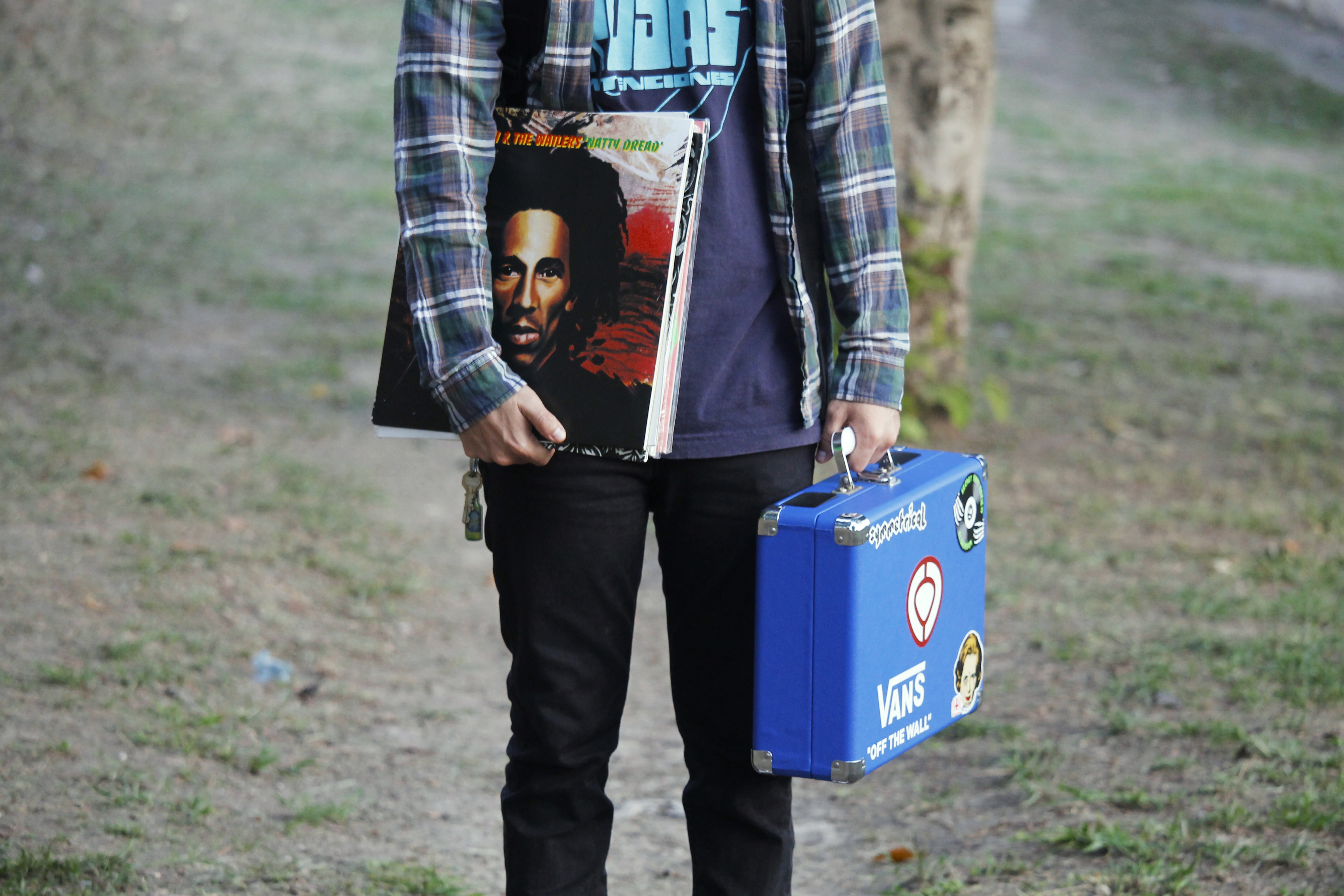A person carrying a blue case and stack of records, including one by Bob Marley