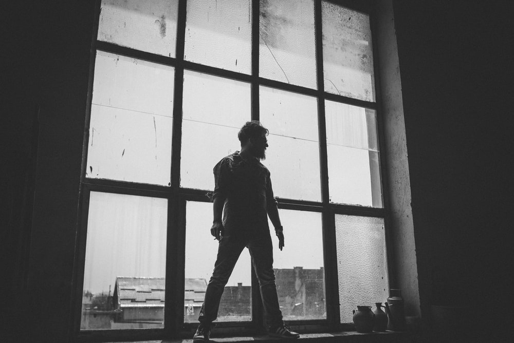 man standing against the glass window grayscale photography