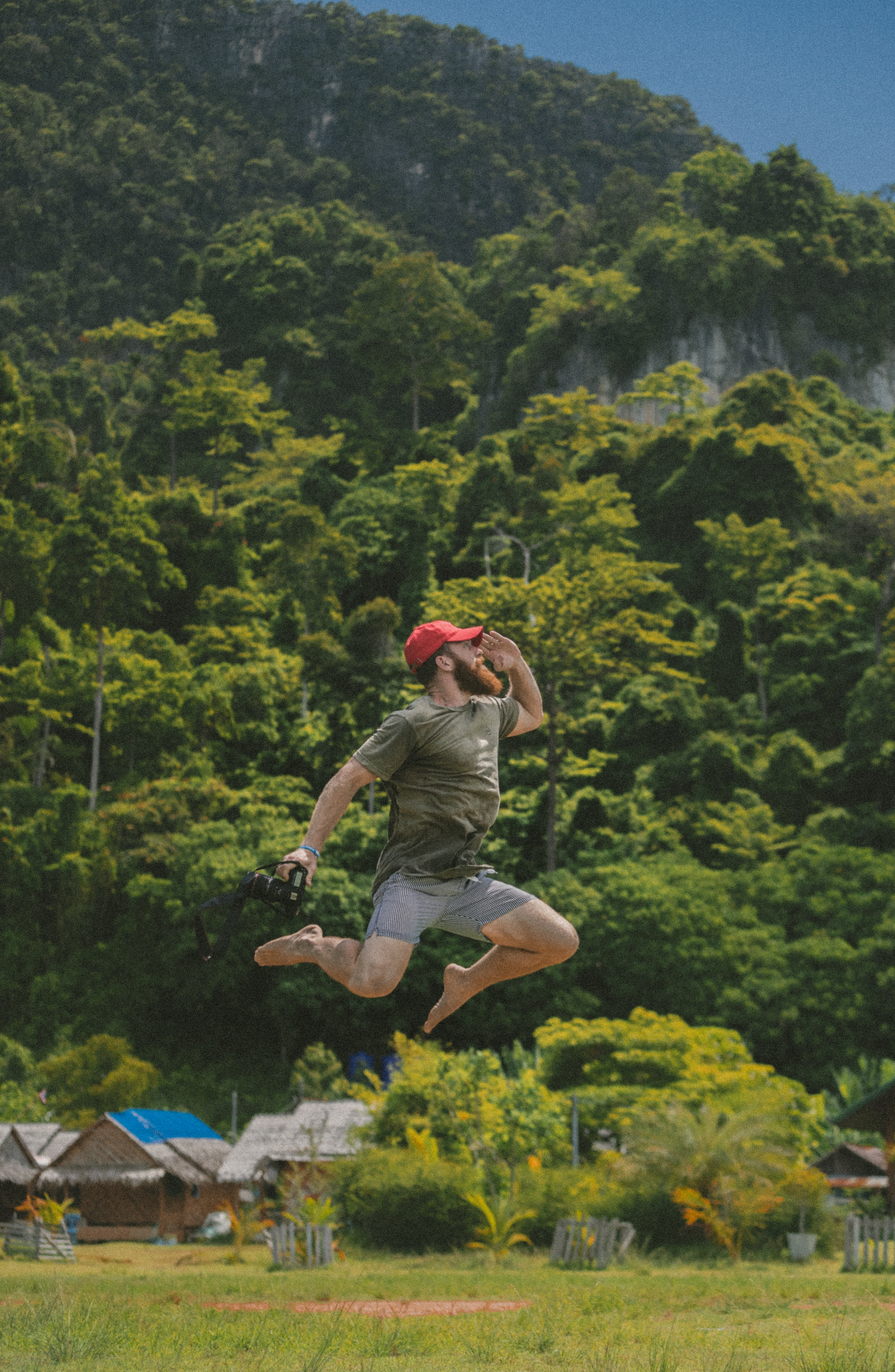 A bearded man in a red baseball cap holding a camera jumps before green hills