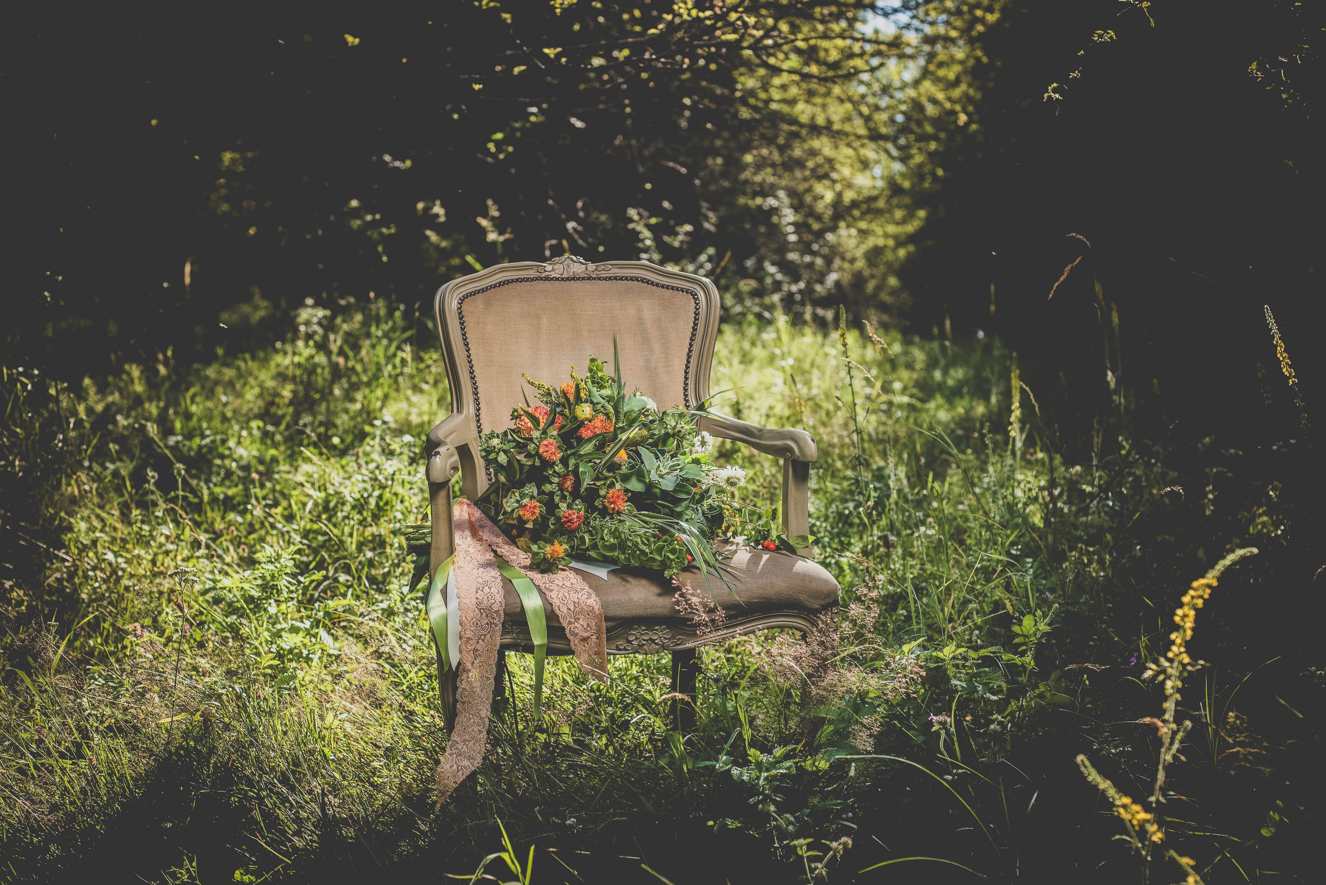 A bouquet of orange flowers on an elegant chair standing in tall grass