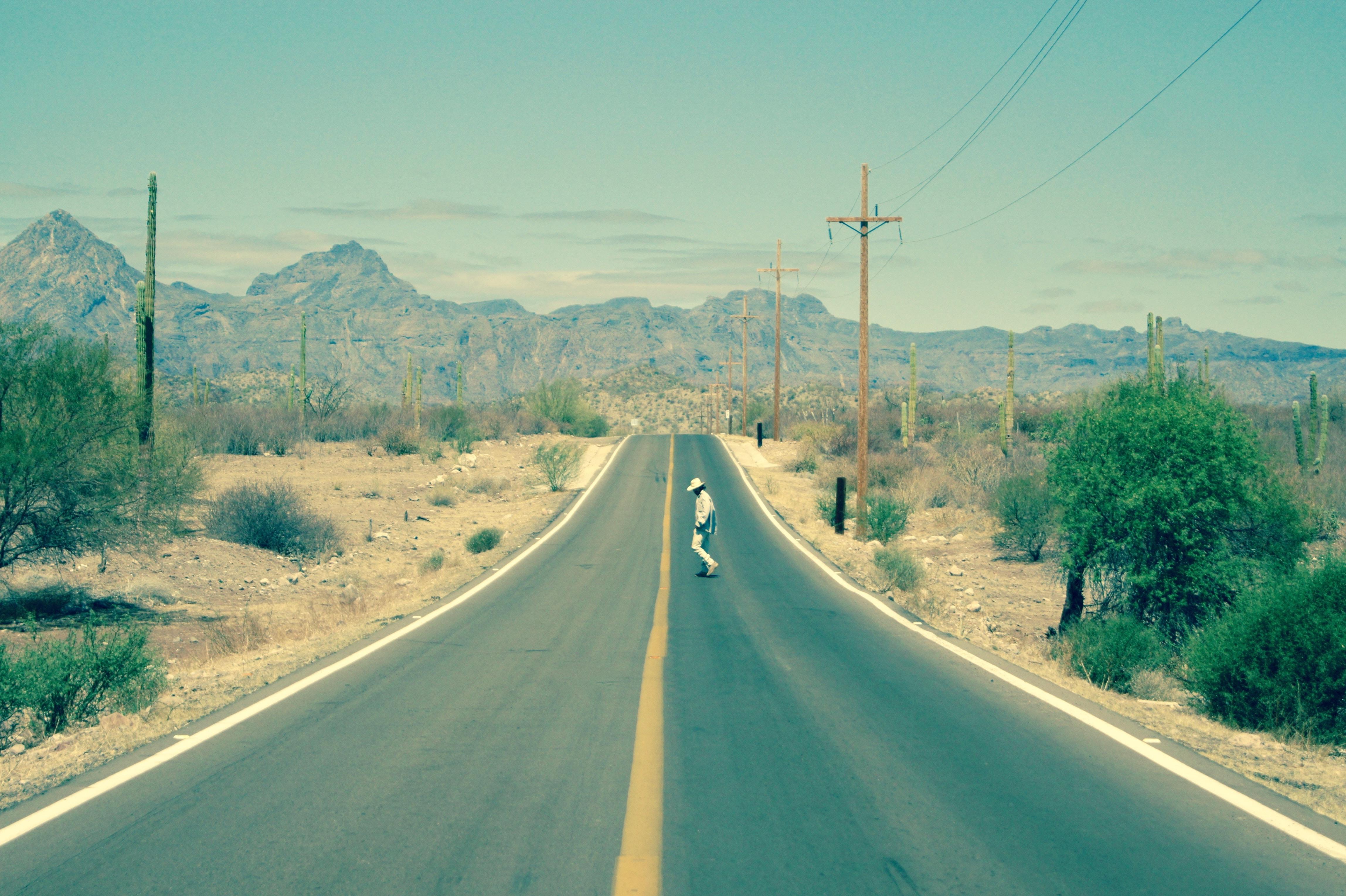 Hiker crosses the road in a desolate desert landscape