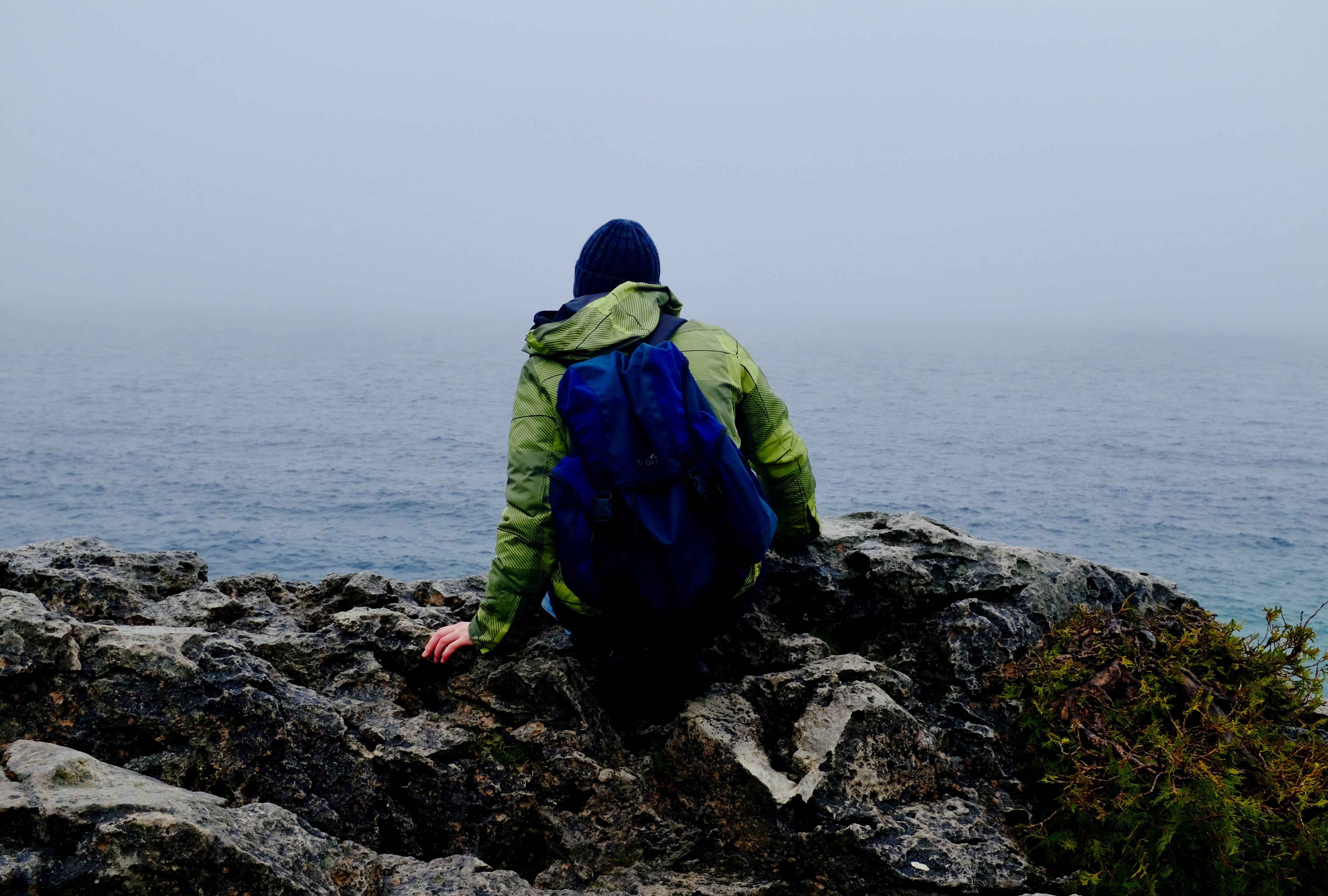 A person sitting on a rock by the sea with a foggy sky at The Grotto