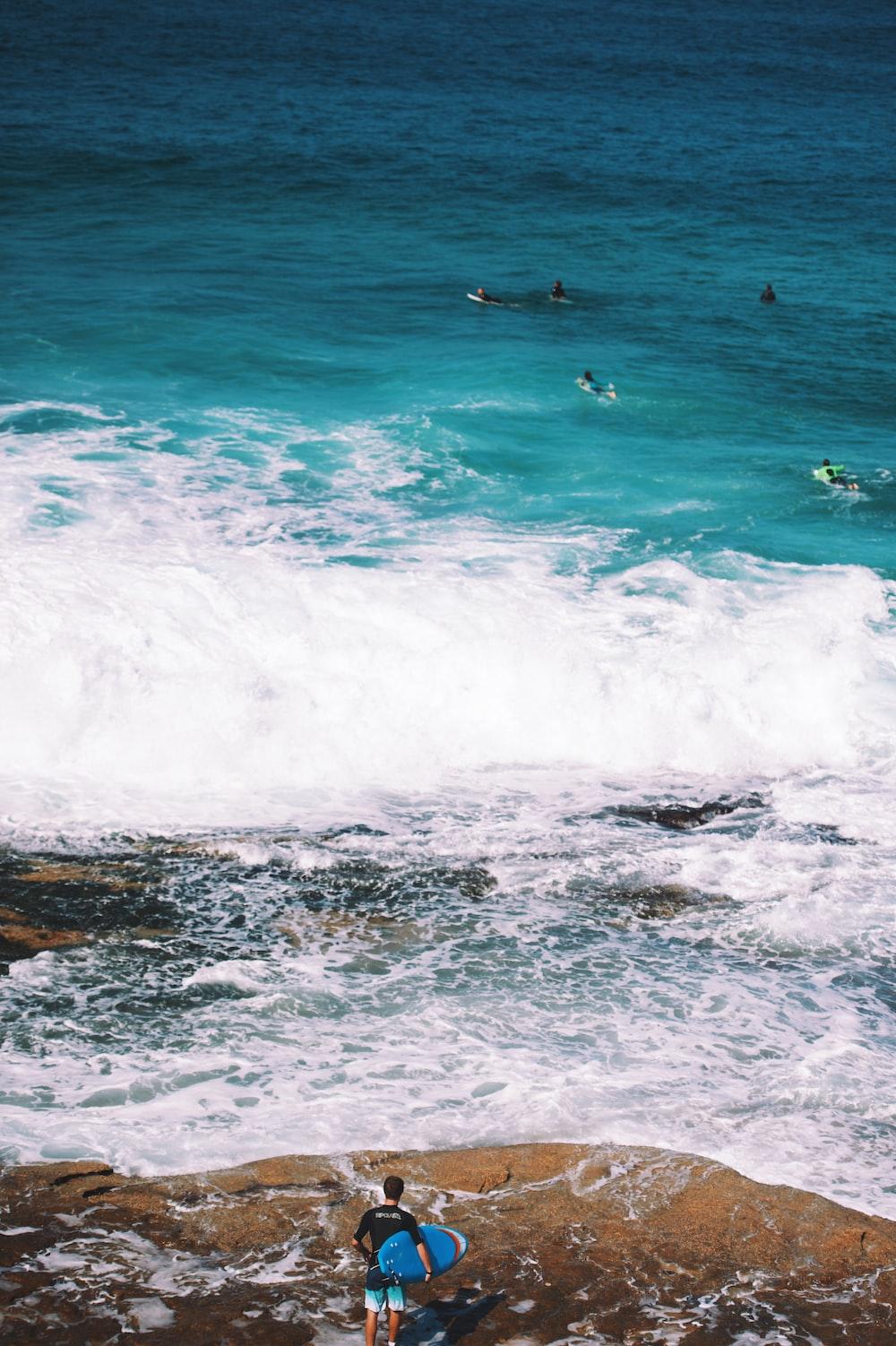 man holding blue surfboard standing on seashore