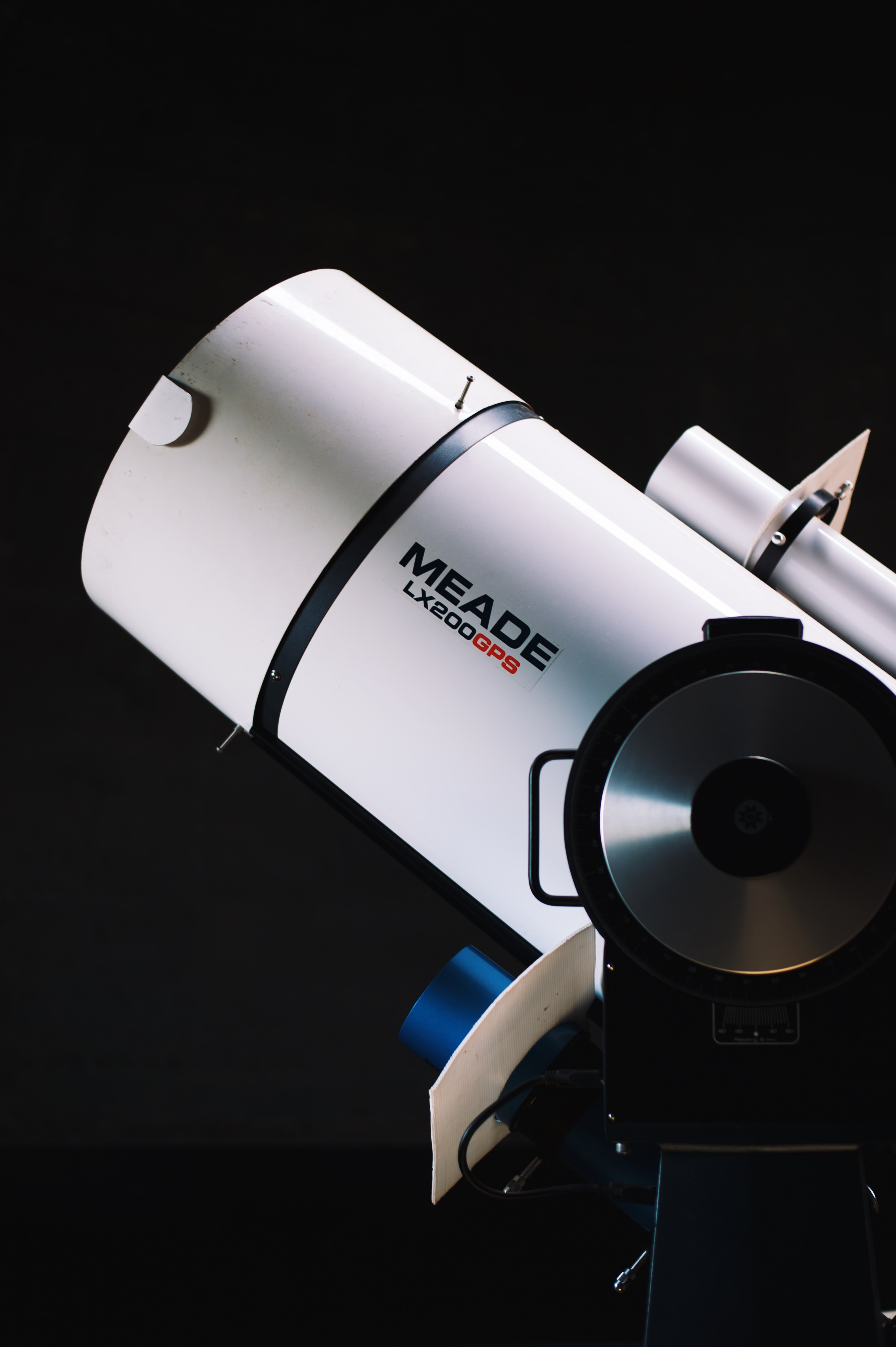 white Meade LX200GPS telescope beside black wall