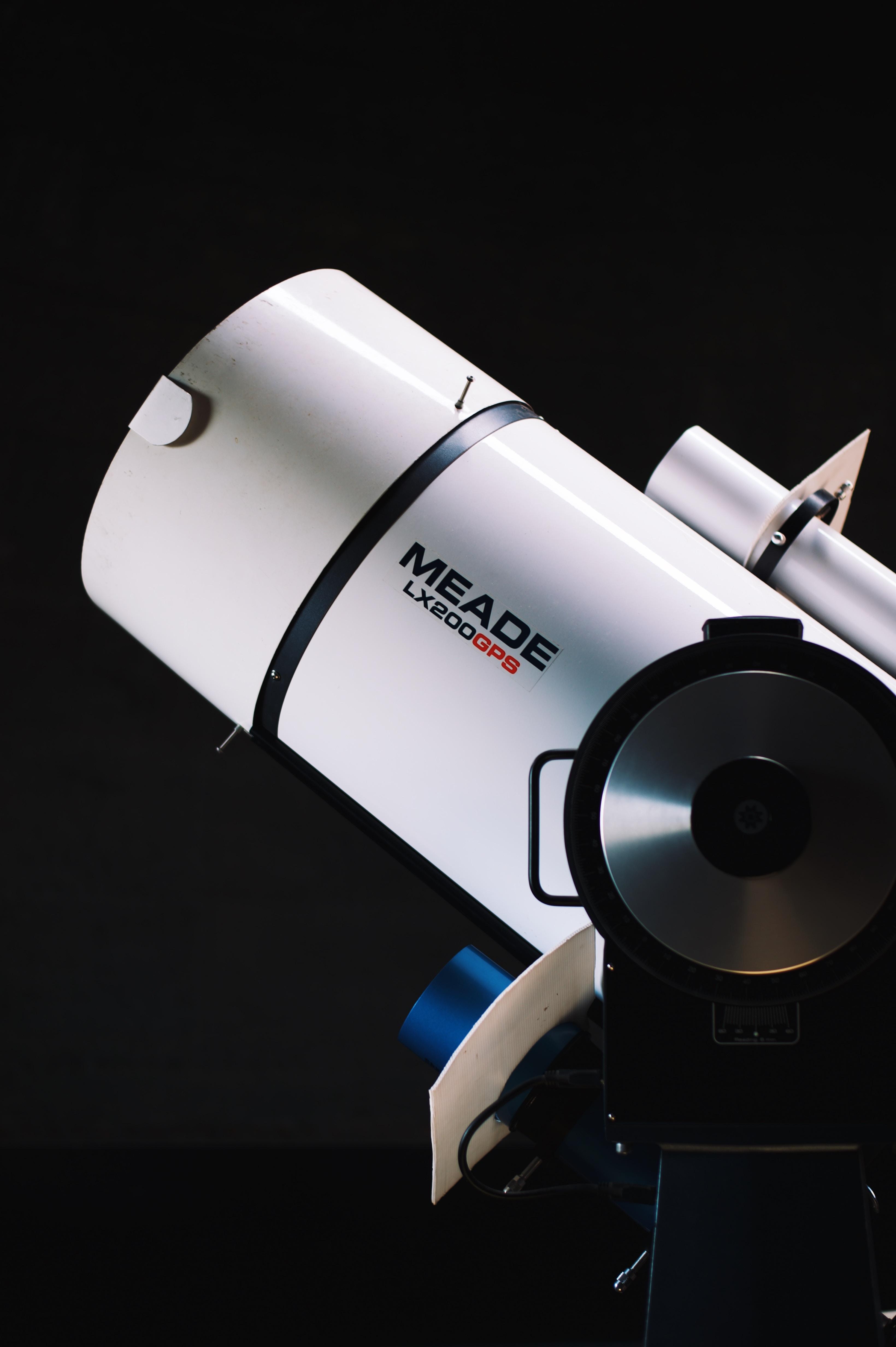 white Meade LX200GPS telescope beside black wall