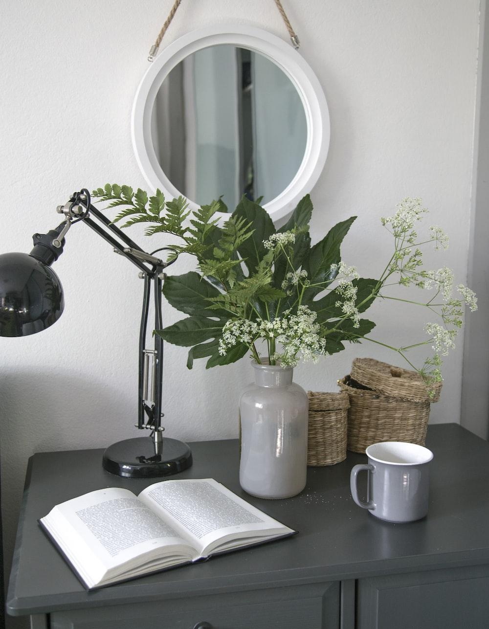 silver and black desk lamp beside white ceramic mug on black wooden table