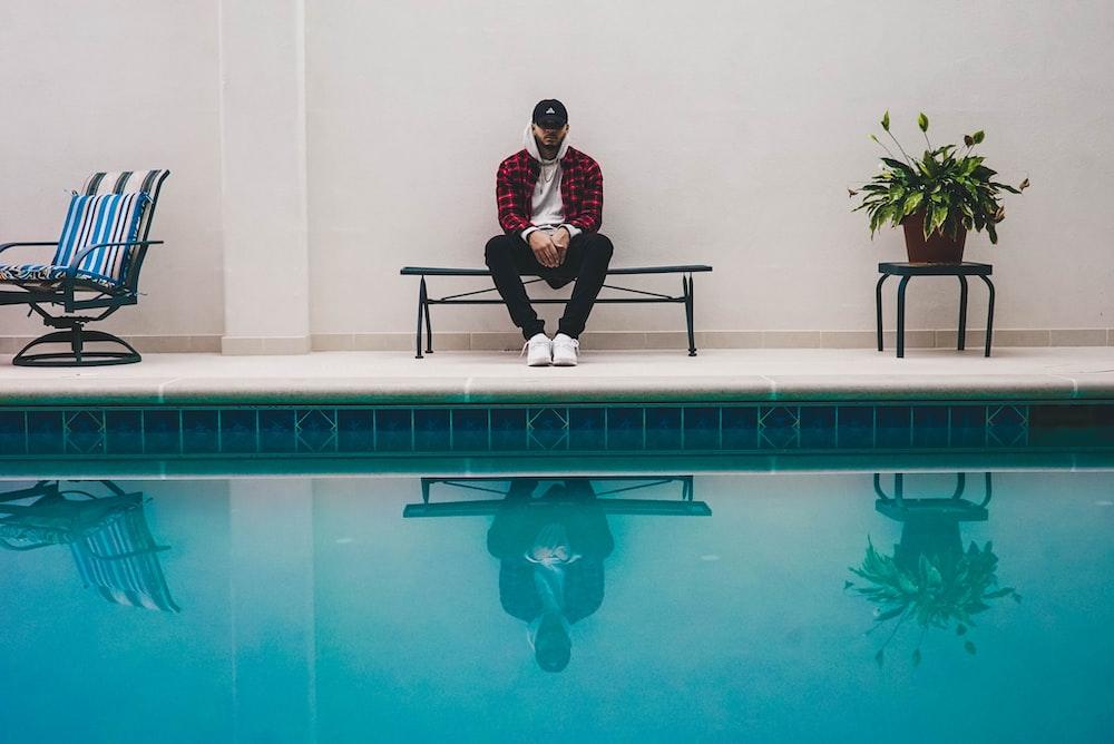 man sitting on black bench near pool