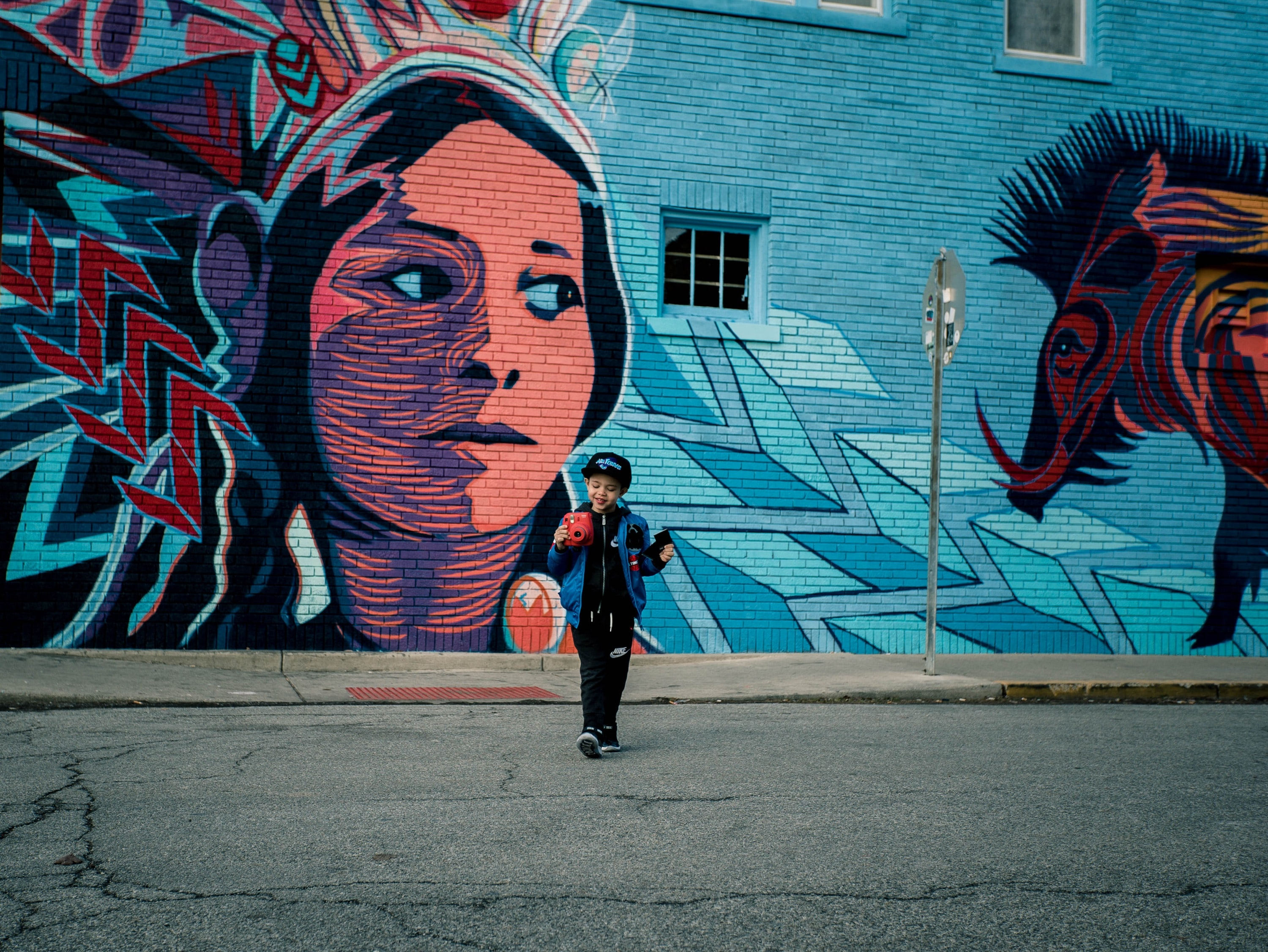 Young boy in cap standing on pavement near graffiti mural with blue background and woman's face