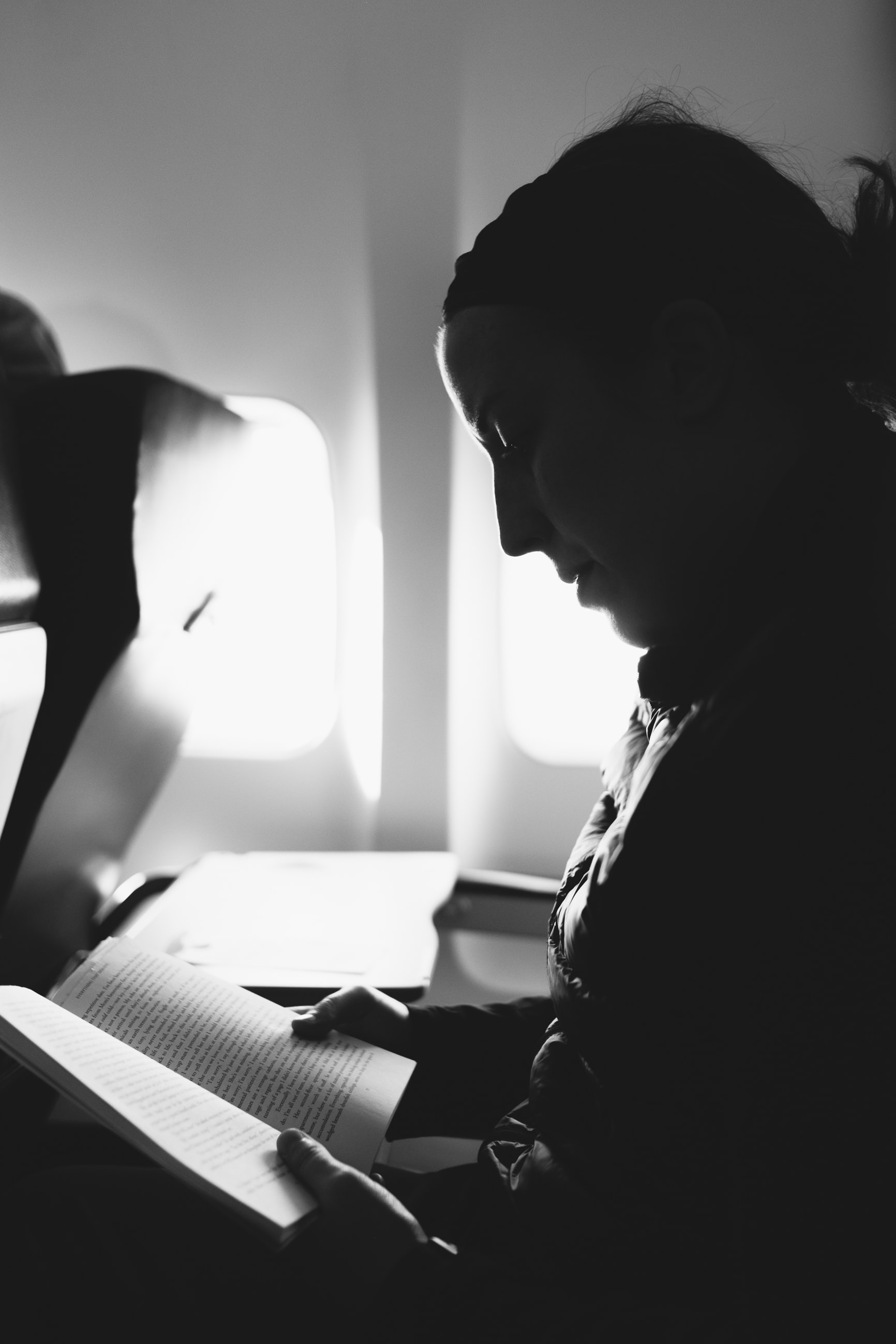 Black and white shot of man reading book in aeroplane