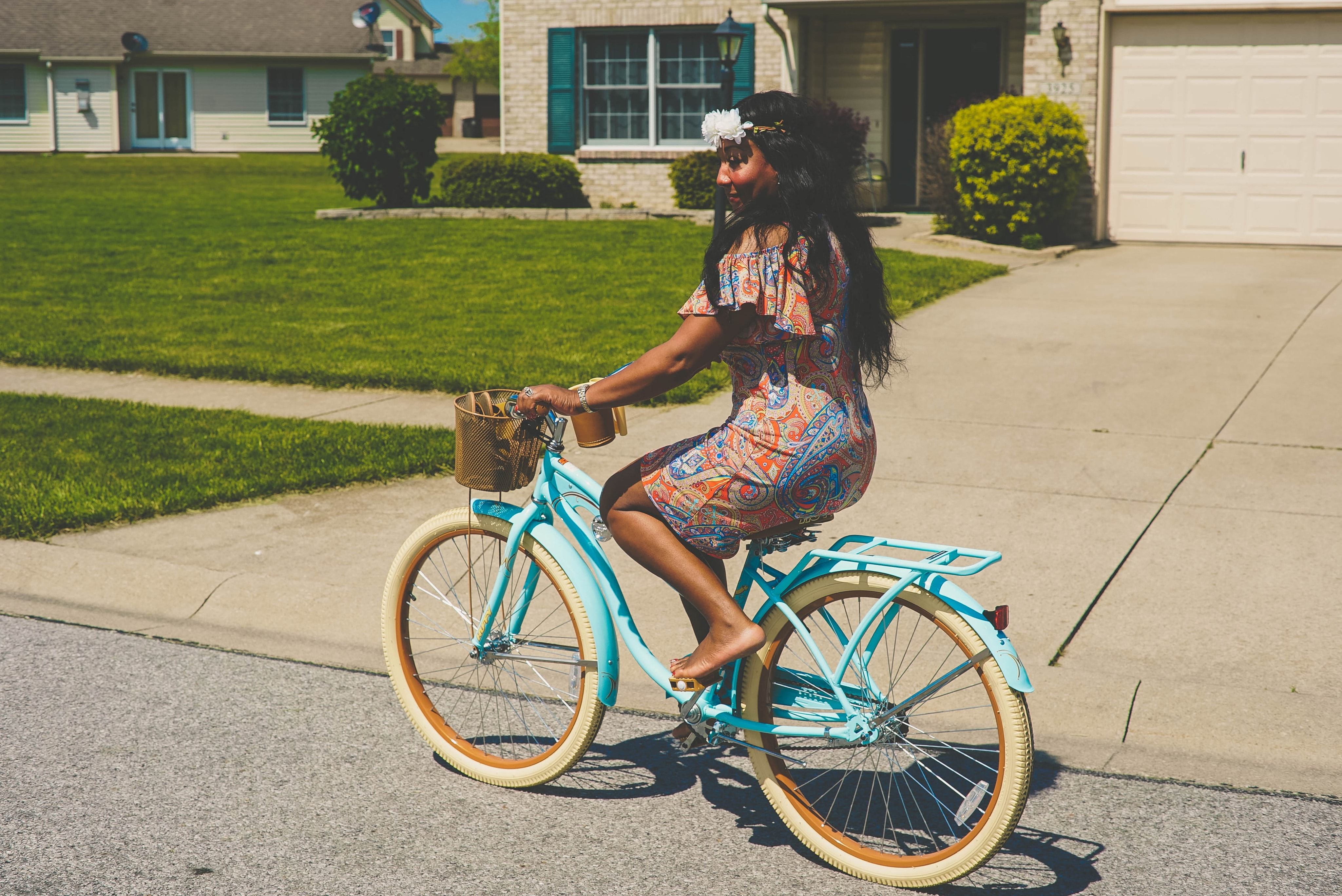 woman in brown and blue dress riding blue bicycle