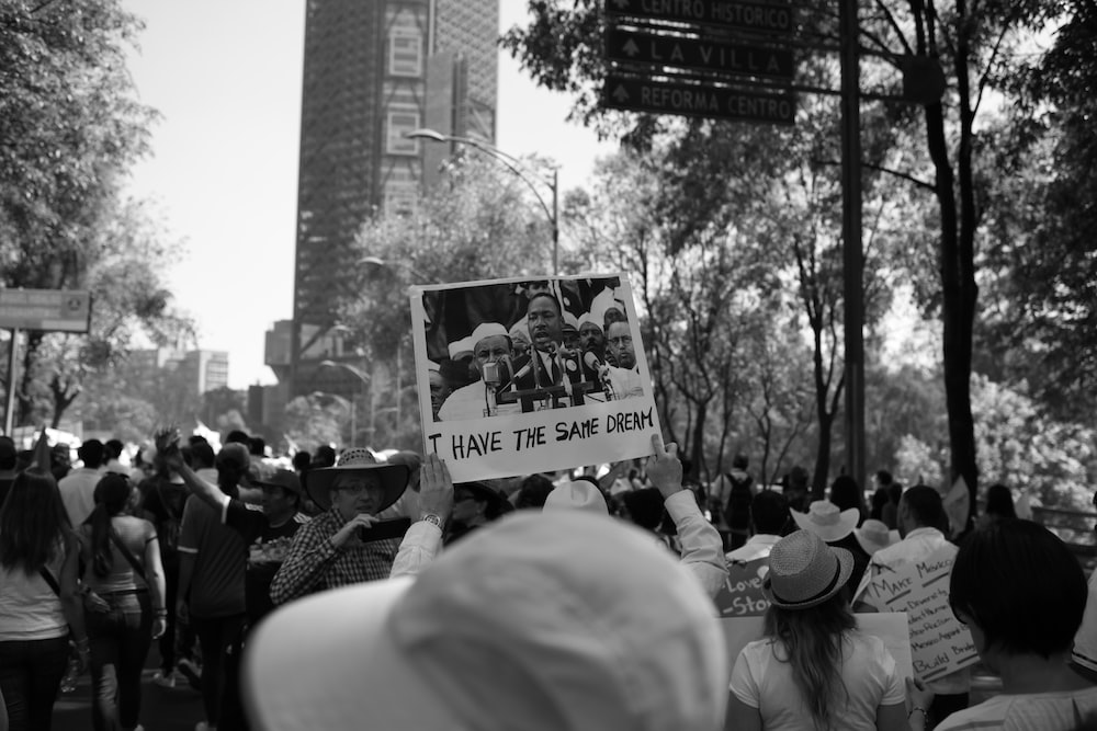 A crowd at a protest in Mexico City and a sign picturing Martin Luther King, Jr.