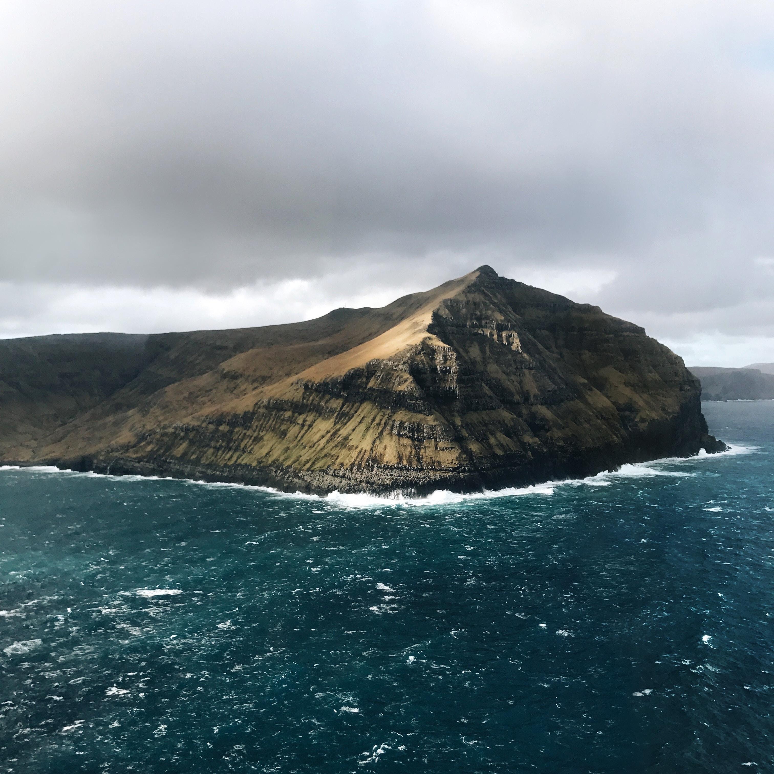 A cliff over choppy azure sea water in the Faroe Islands