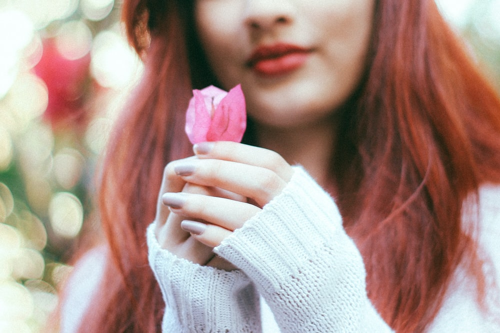 woman holding pink rose