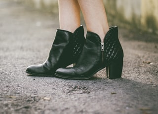 woman in black chunky heels boots standing on gray floor