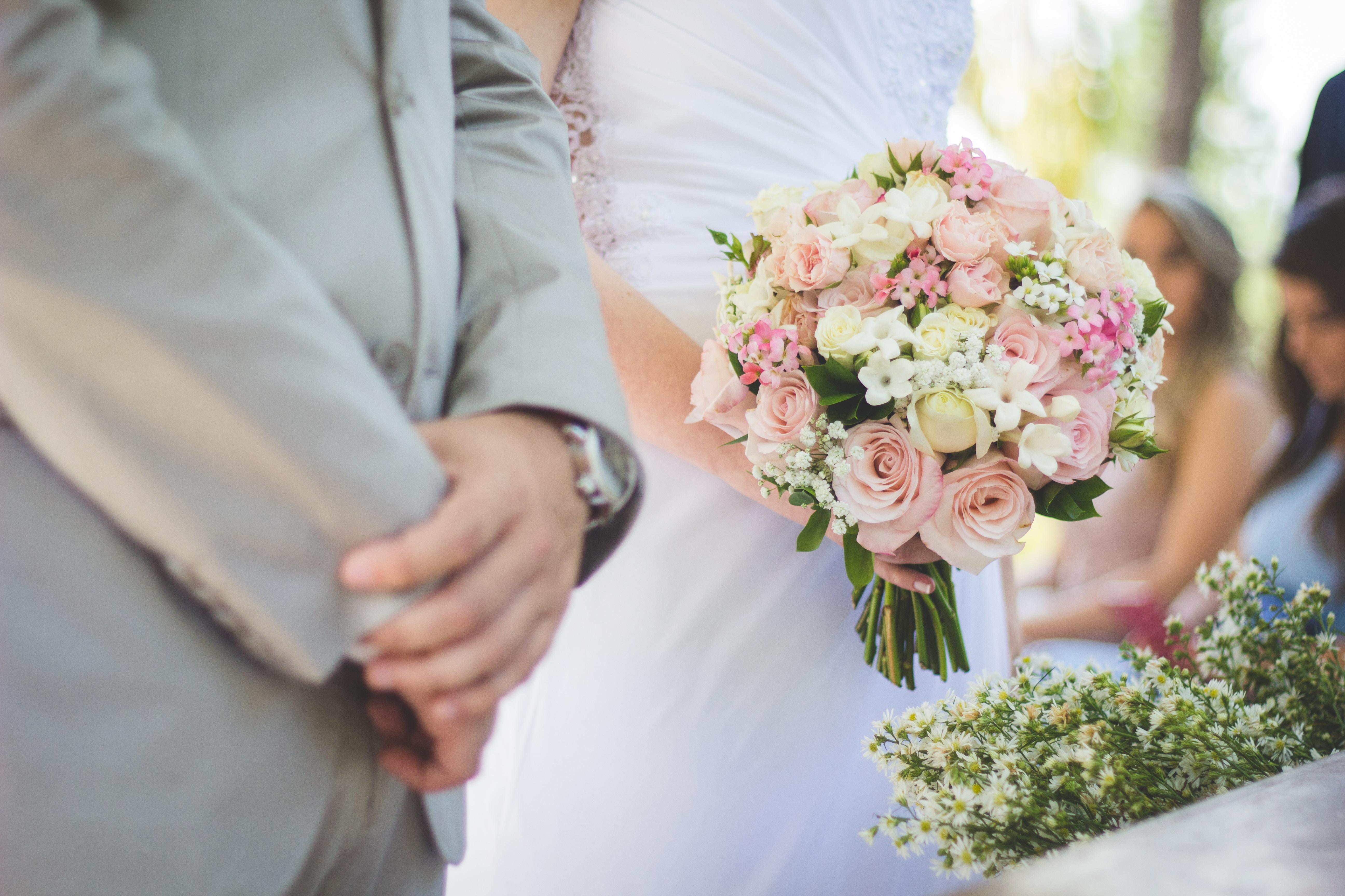 Guests blurred behind bride and groom on Marília wedding day