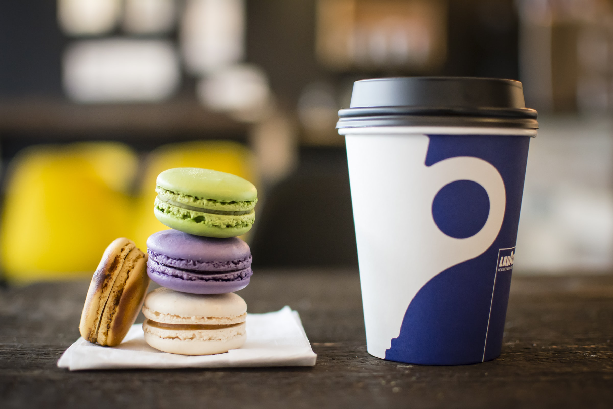 Colorful macarons stacked next to a cup of coffee