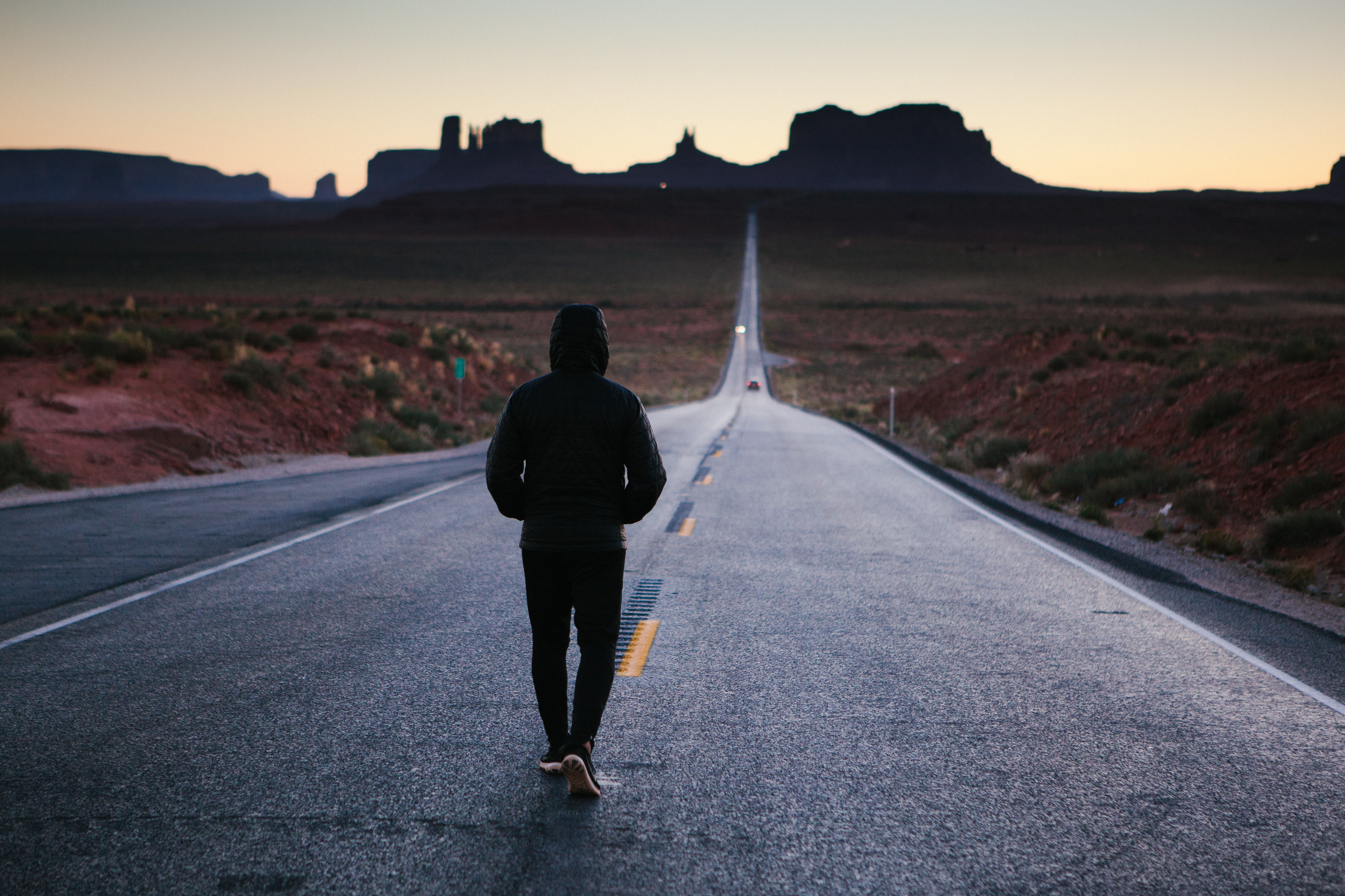 Anonymous person walking alone down a desert country road