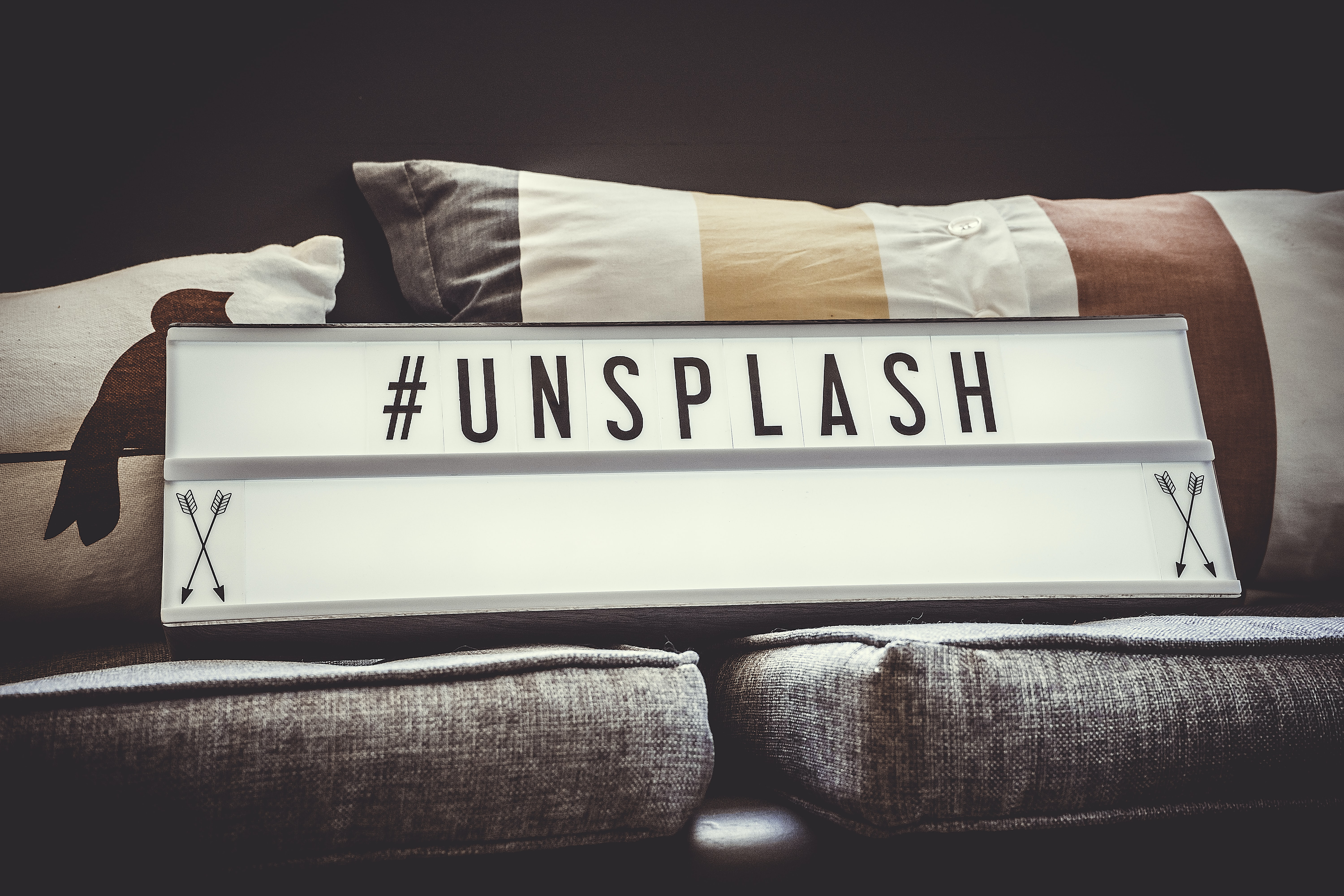 "Small marquee reading ""#unsplash"" sits on a gray couch with two decorative pillows"