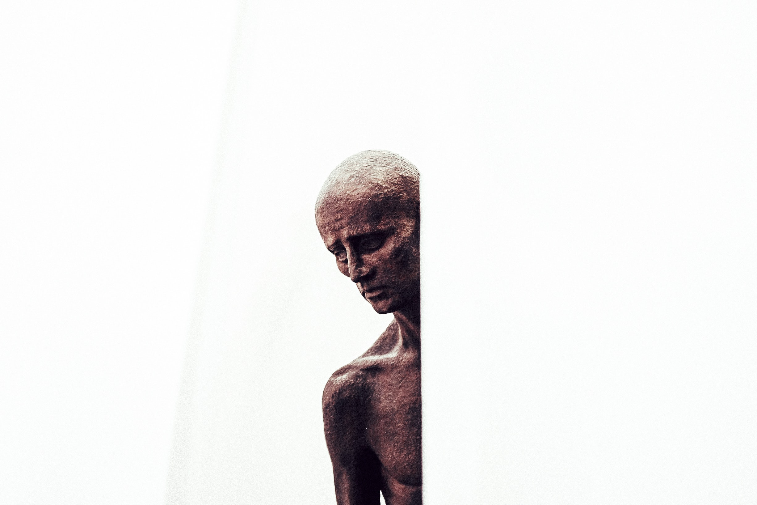 Somber copper statue of a naked man at an art museum