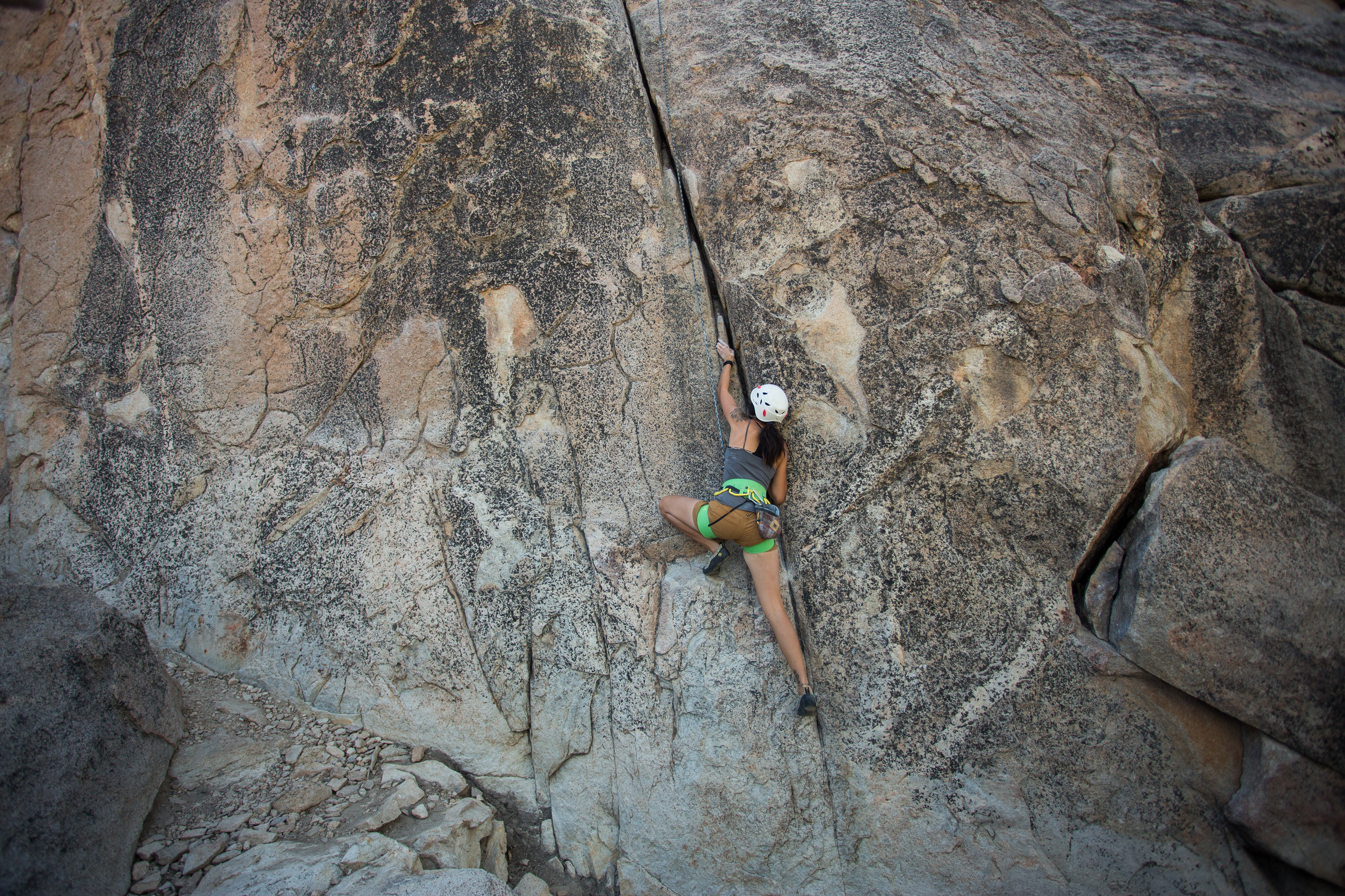 A woman wearing a white helmet and green shorts rock climbing the side of a mountain in Big Bear Lake