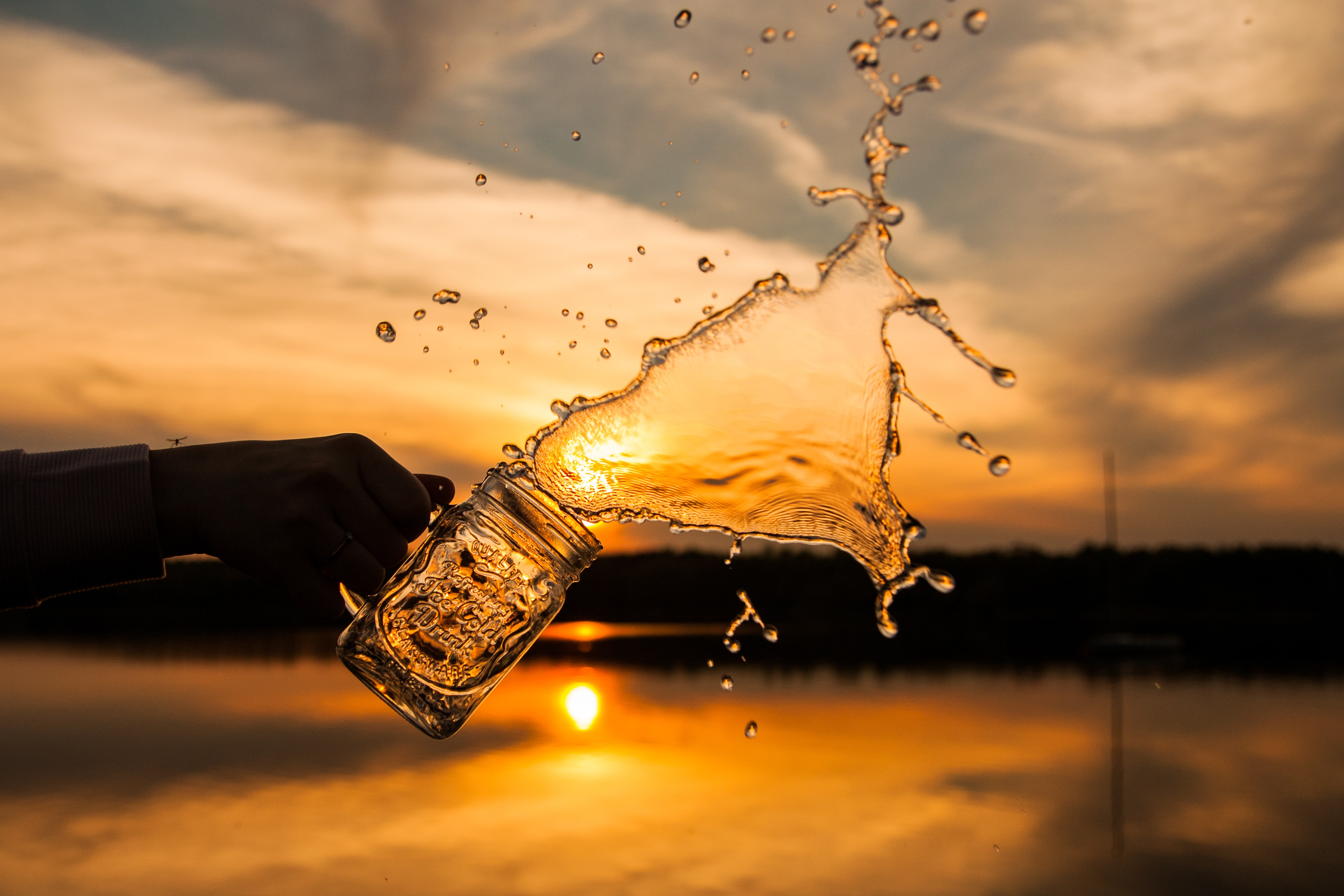 Water being splashed out of a mason jar with a sunset backdrop