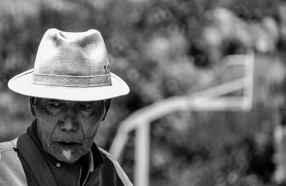 grayscale photo of man wearing hat