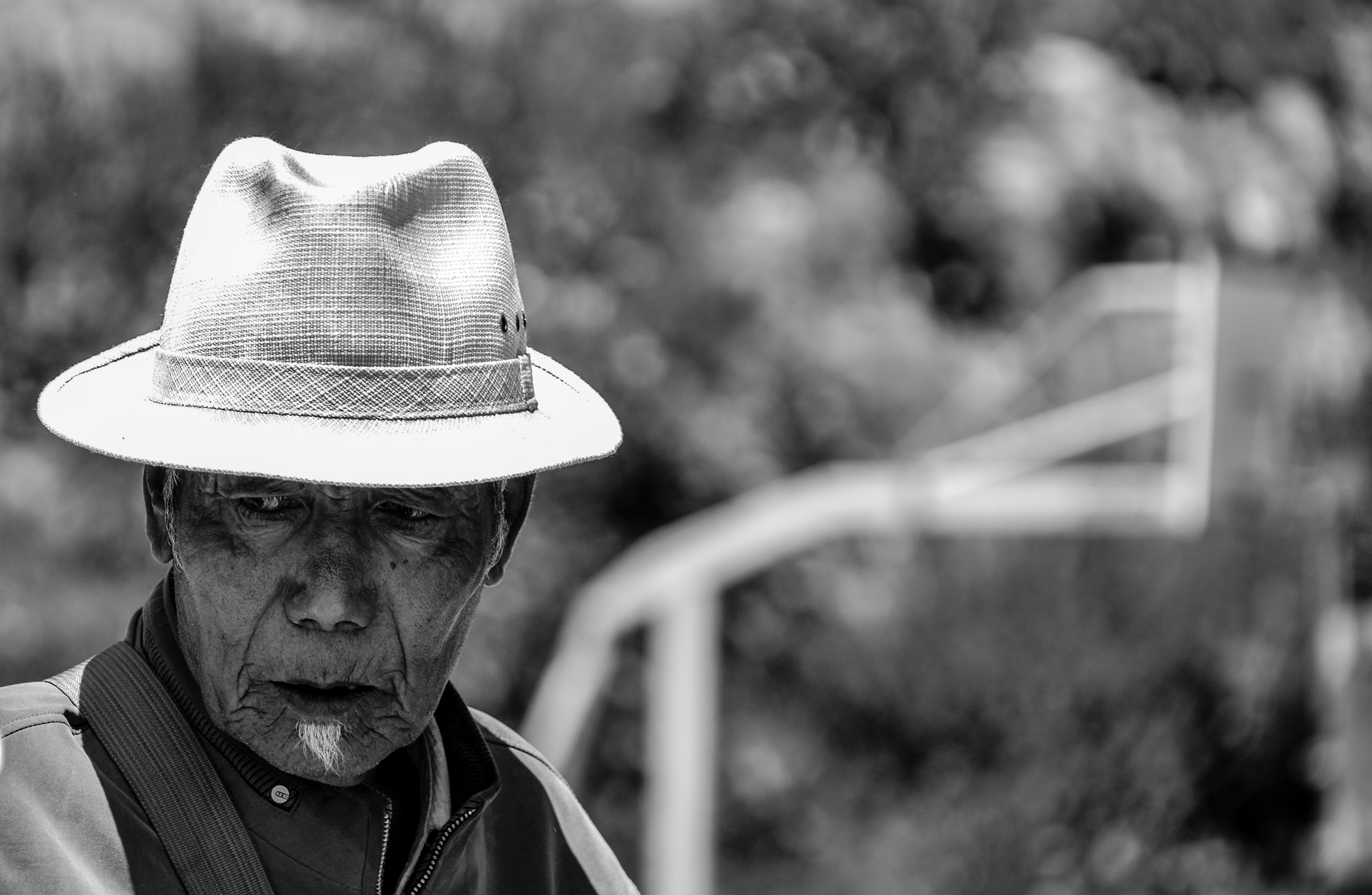 A weathered, old man wearing a fedora hat in Tibet