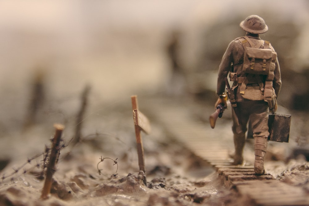 soldier walking on wooden pathway surrounded with barbwire selective focus photography