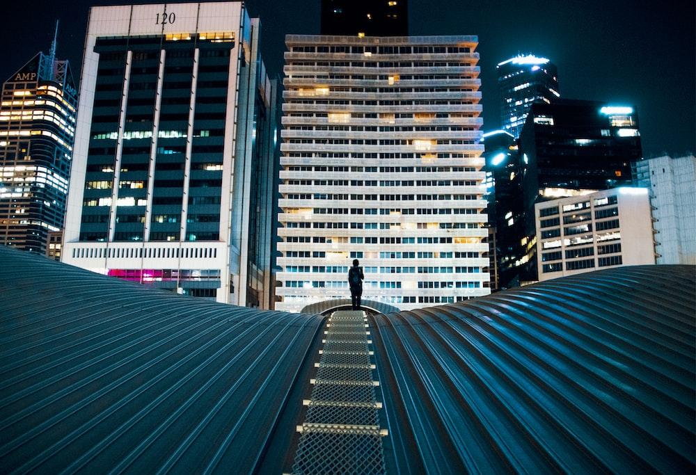 背景に都市の建物と建物の屋根の上に立っている人