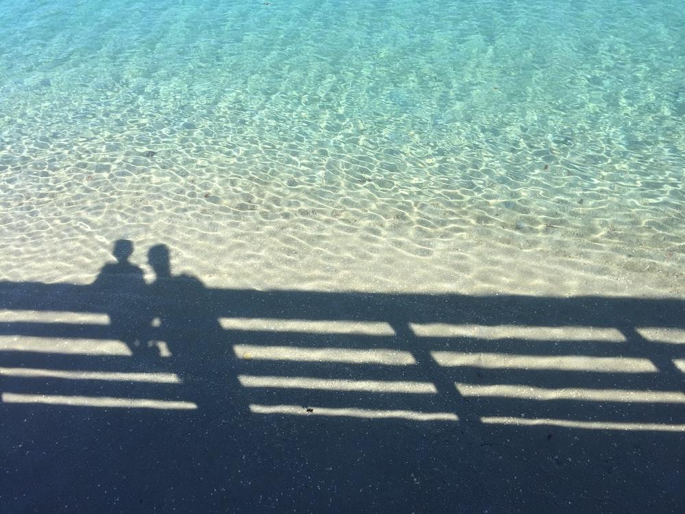 shadow of boy and man near fence