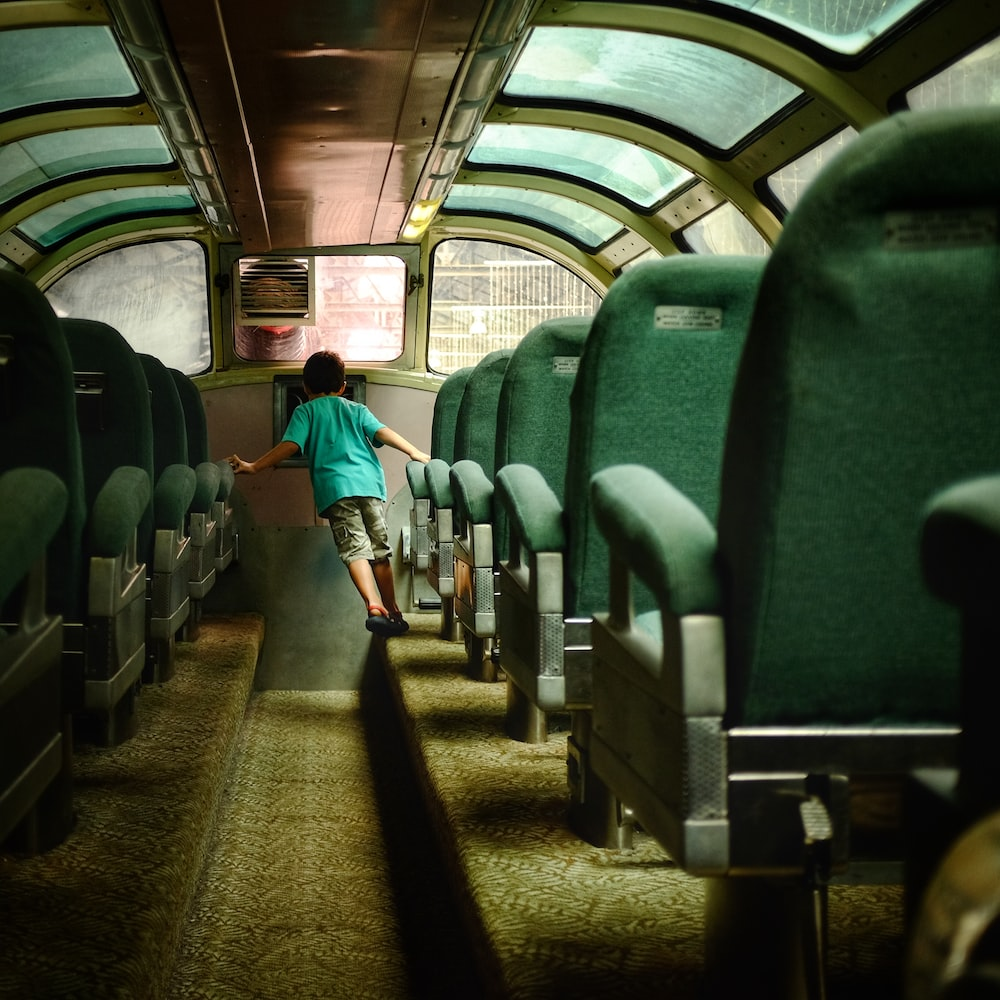boy walking inside bus with green seats
