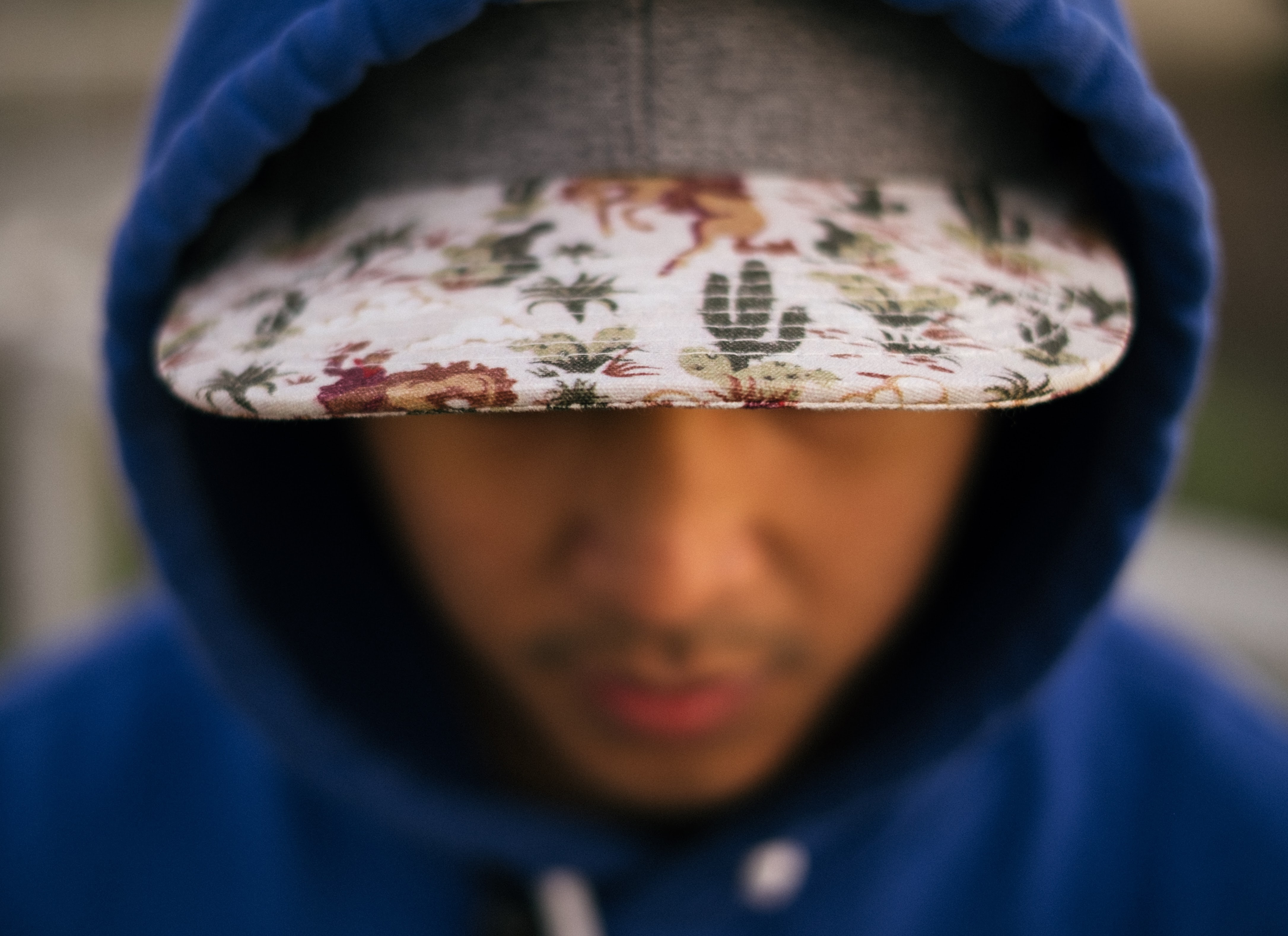 A person in a baseball cap and blue hoodie leans forward, displaying the patterned brim