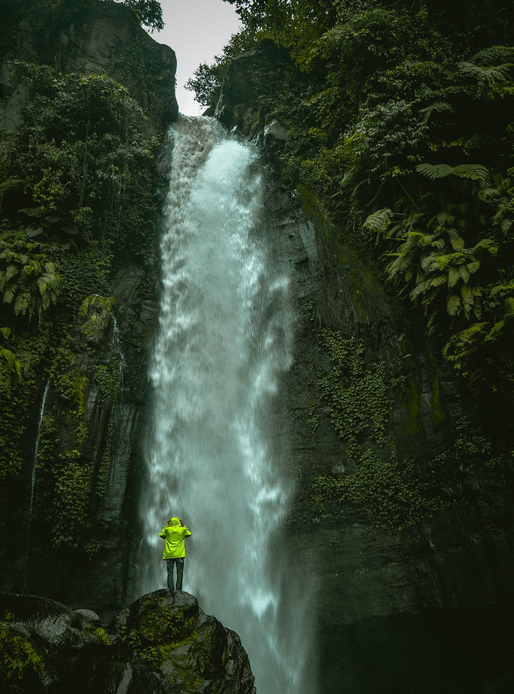 man standing on rock infront of waterfalls