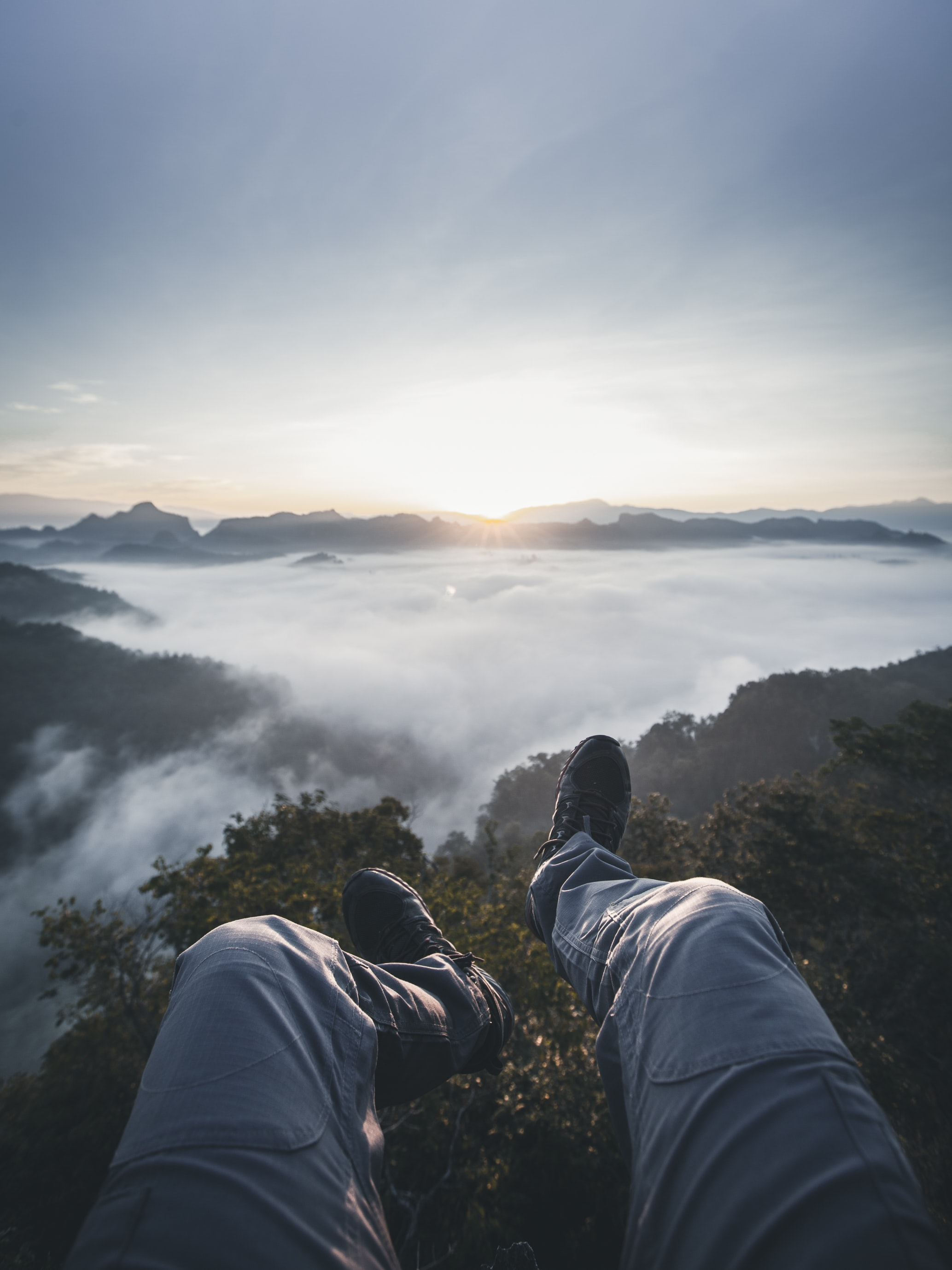 person's feet facing foggy mountain field during golden hour