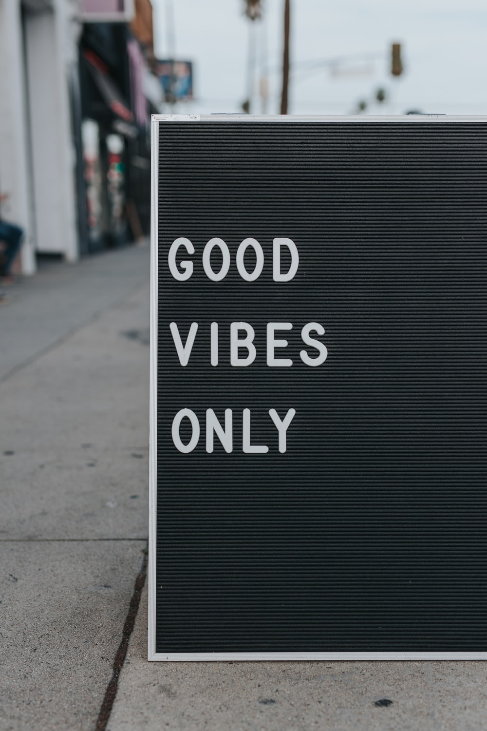 "Sidewalk sign displaying ""Good Vibes Only"" on Sunset Strip"