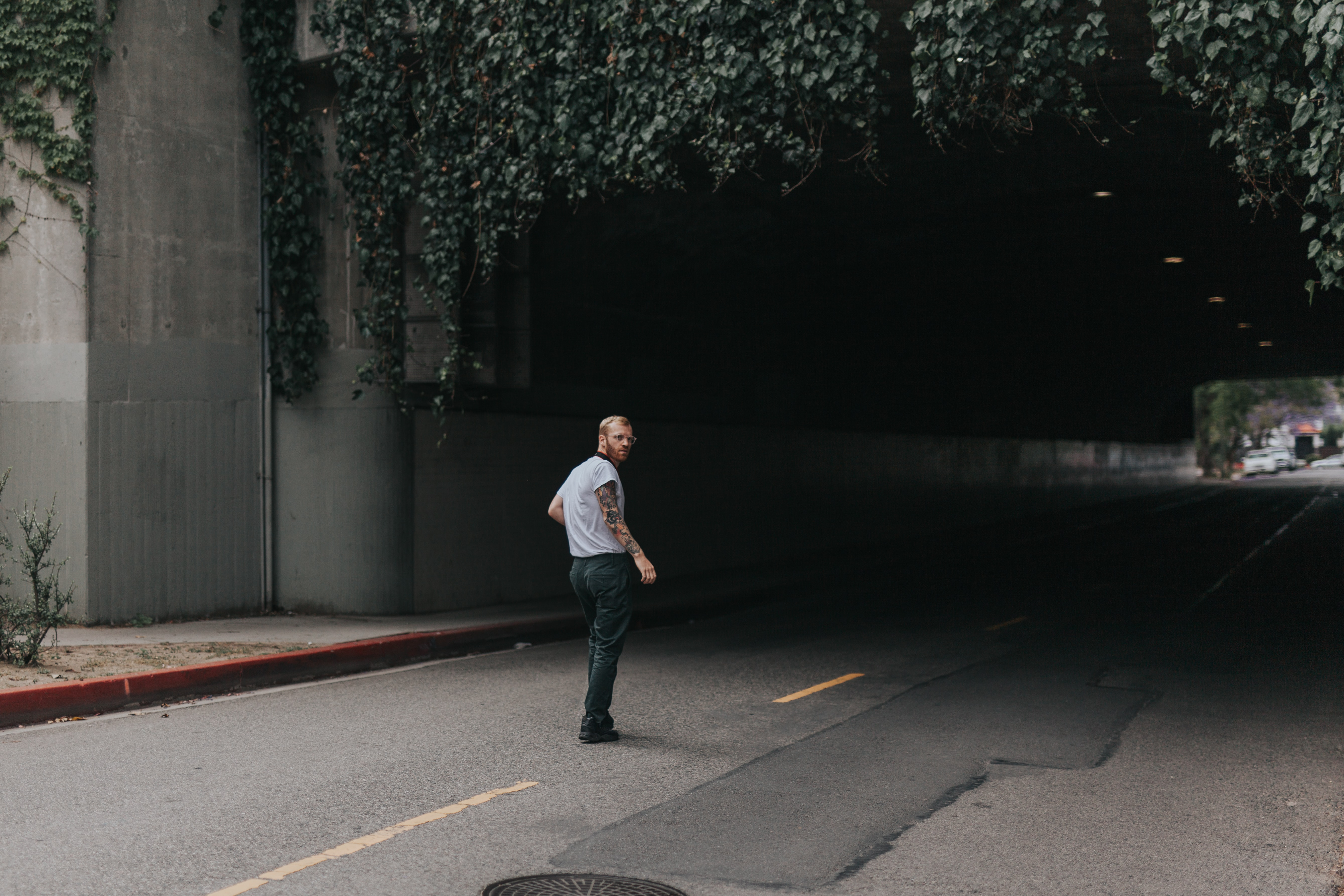 Man with beard and tattoos standing in front of a tunnel road in Los Angeles