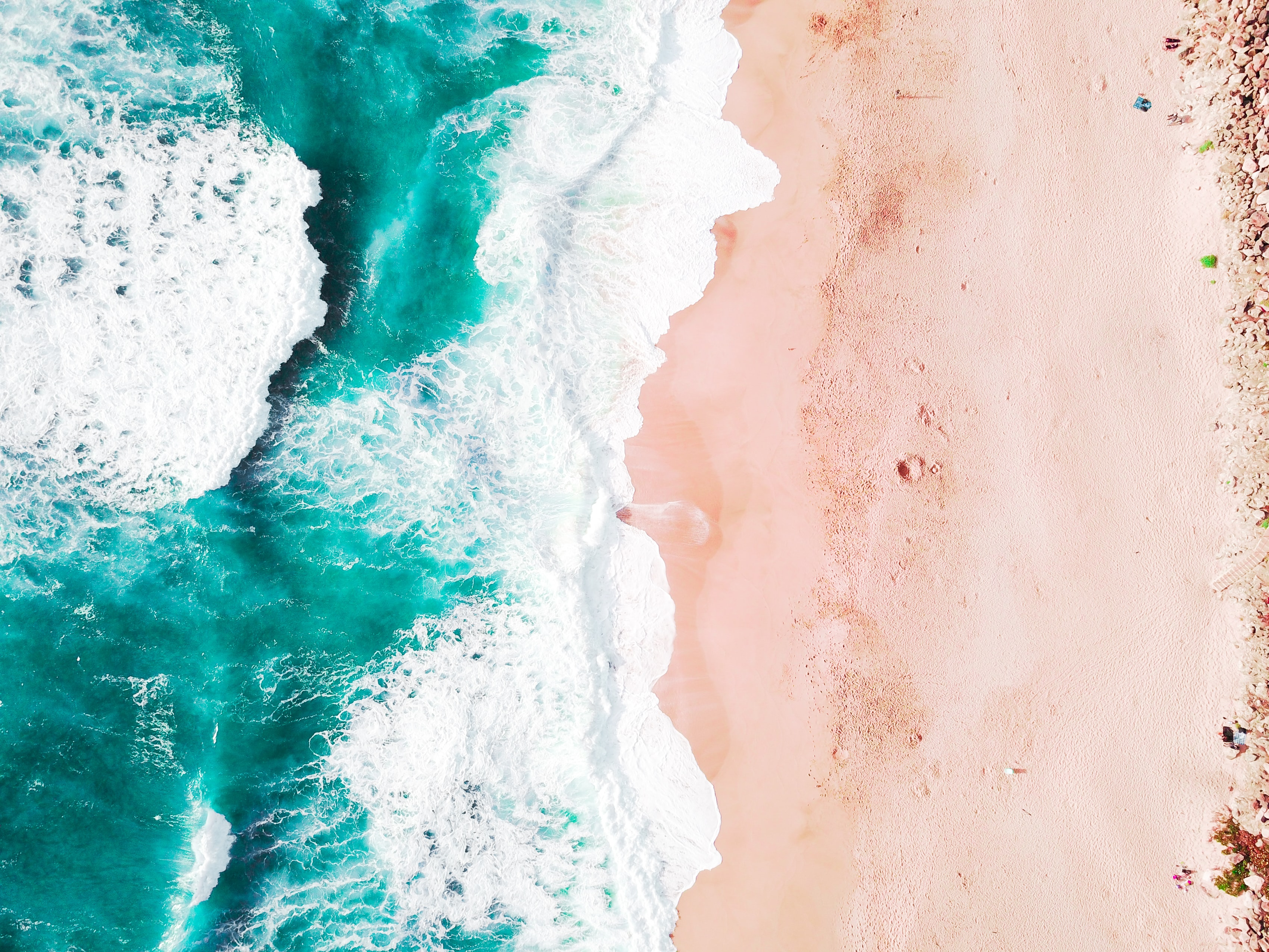 Drone aerial view of the ocean washing on the sand beach in California