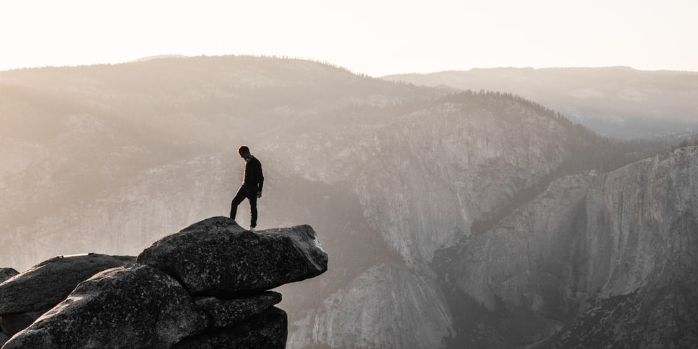 man standing on top of mountain during daytime