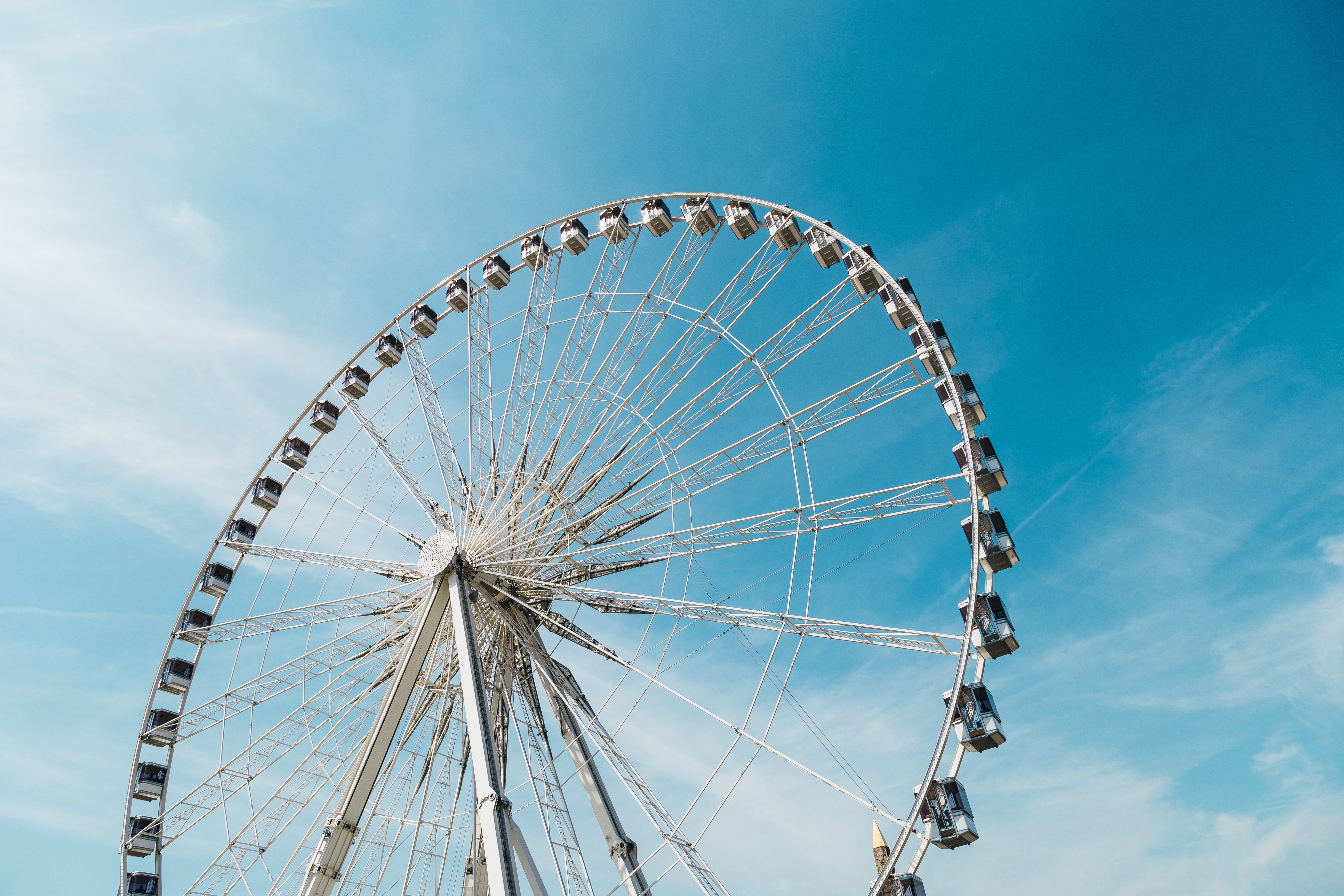 A large Ferris Wheel against a blue sky in Paris