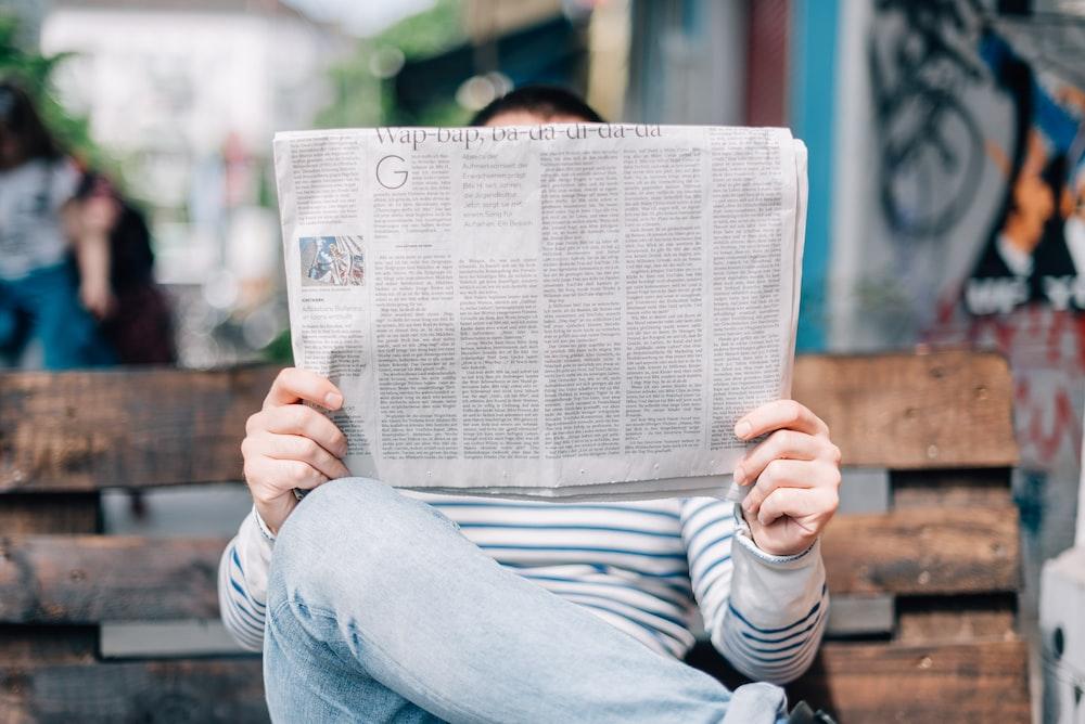 man sitting on bench reading newspaper