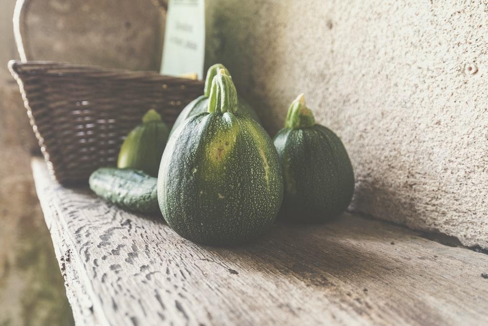four green squash on wooden shelf