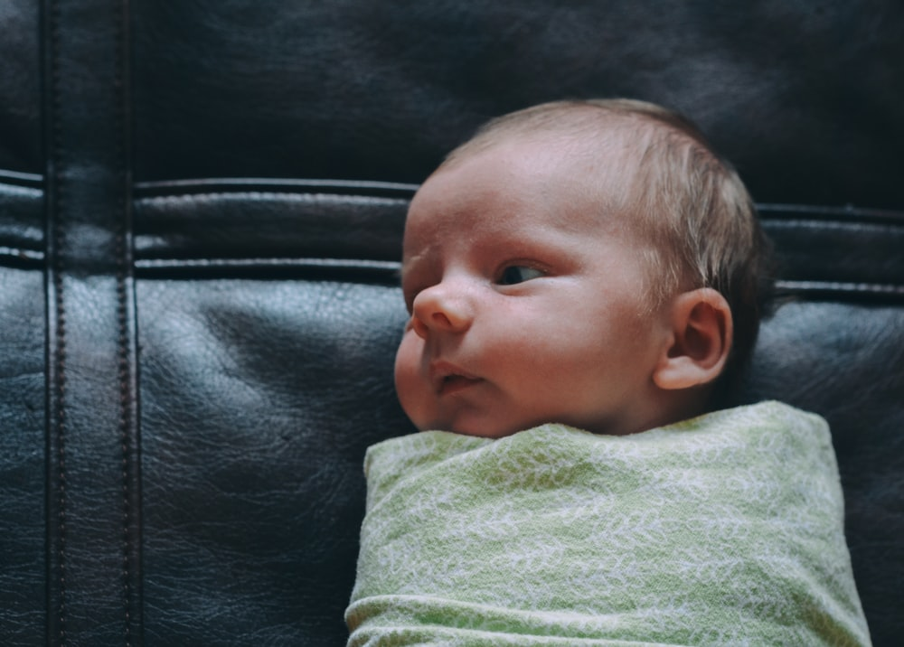 baby covered in green blanket on black leather surface