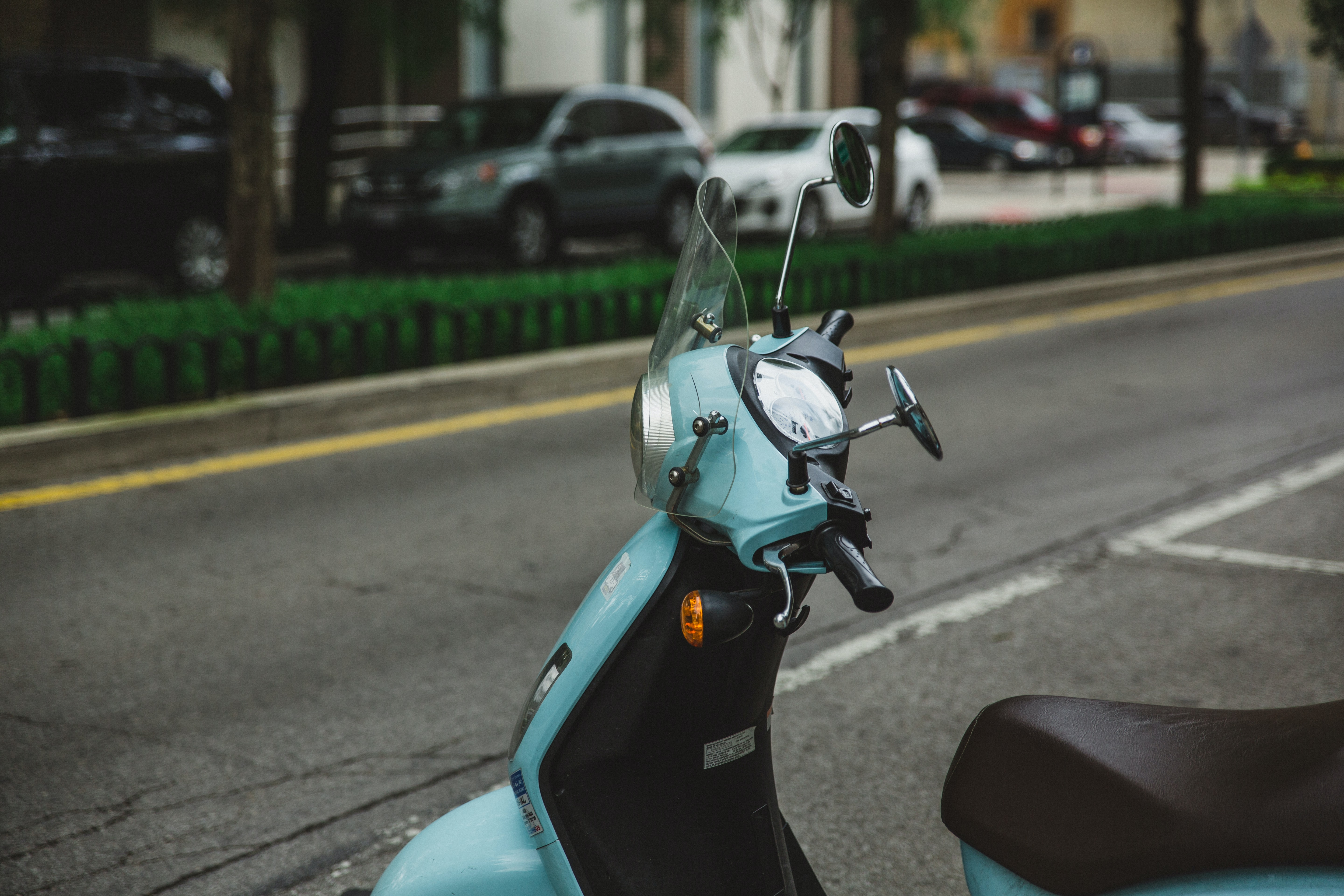 Turquoise blue moped parked on a calm city street