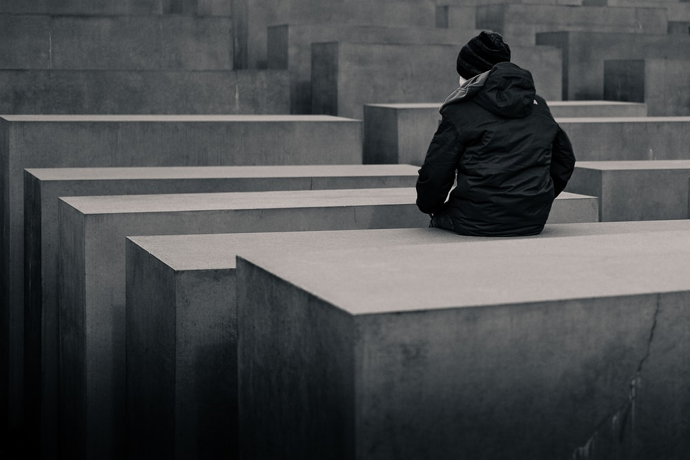 grayscale photo of woman sitting on concrete block
