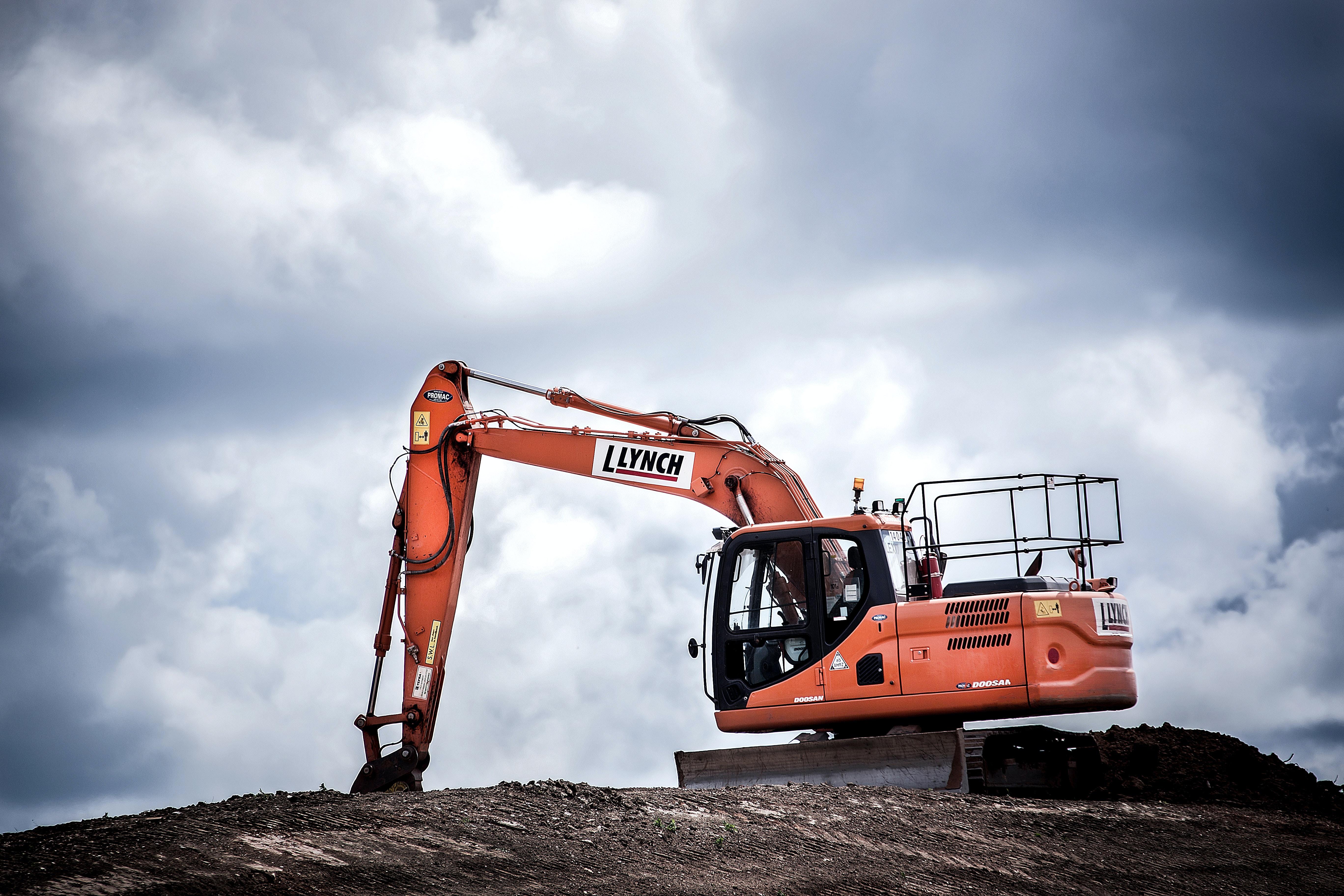 An orange excavator at a construction site