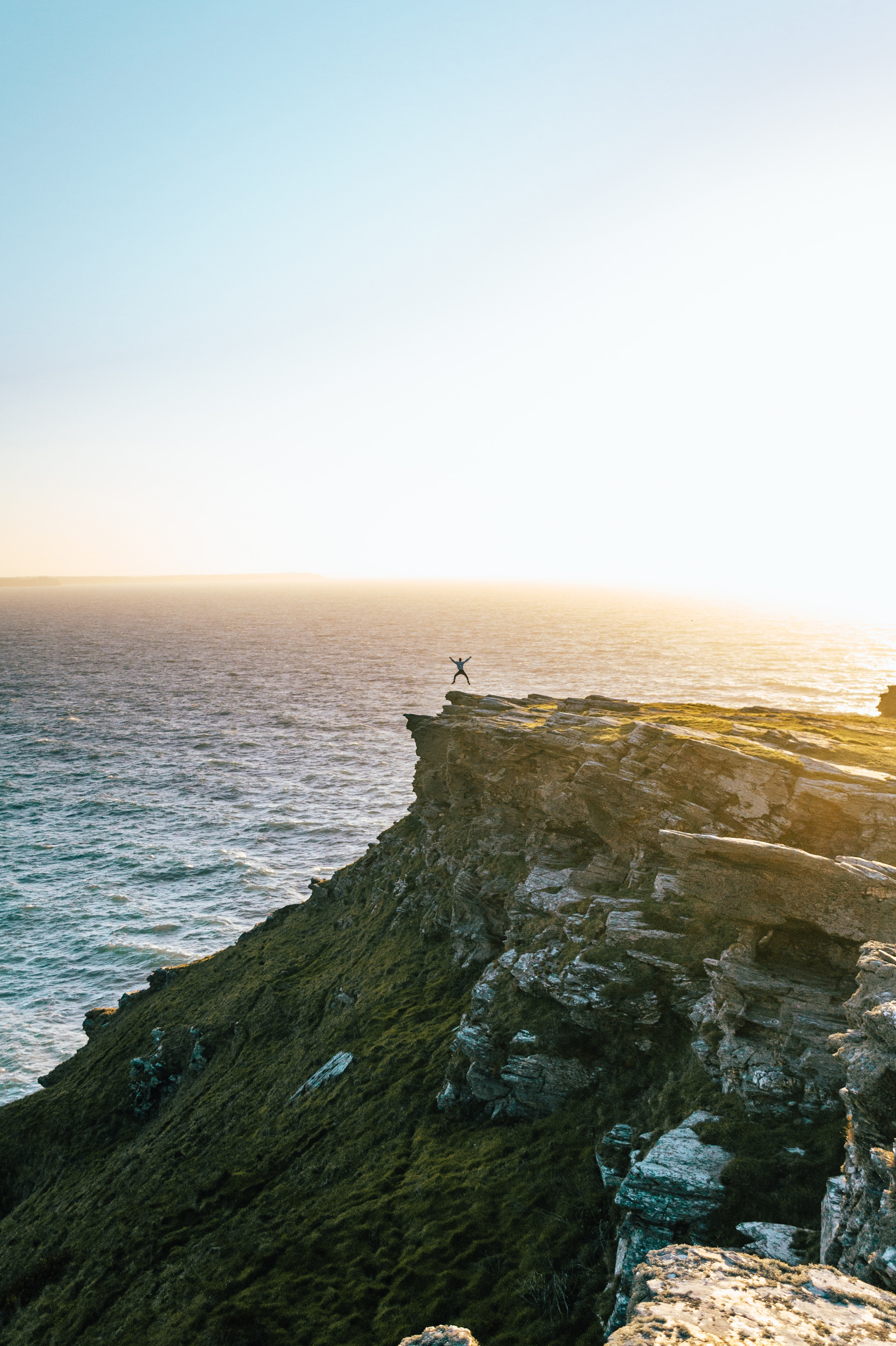 A man jumping in the air at the edge of a cliff at sunset in Tintagel