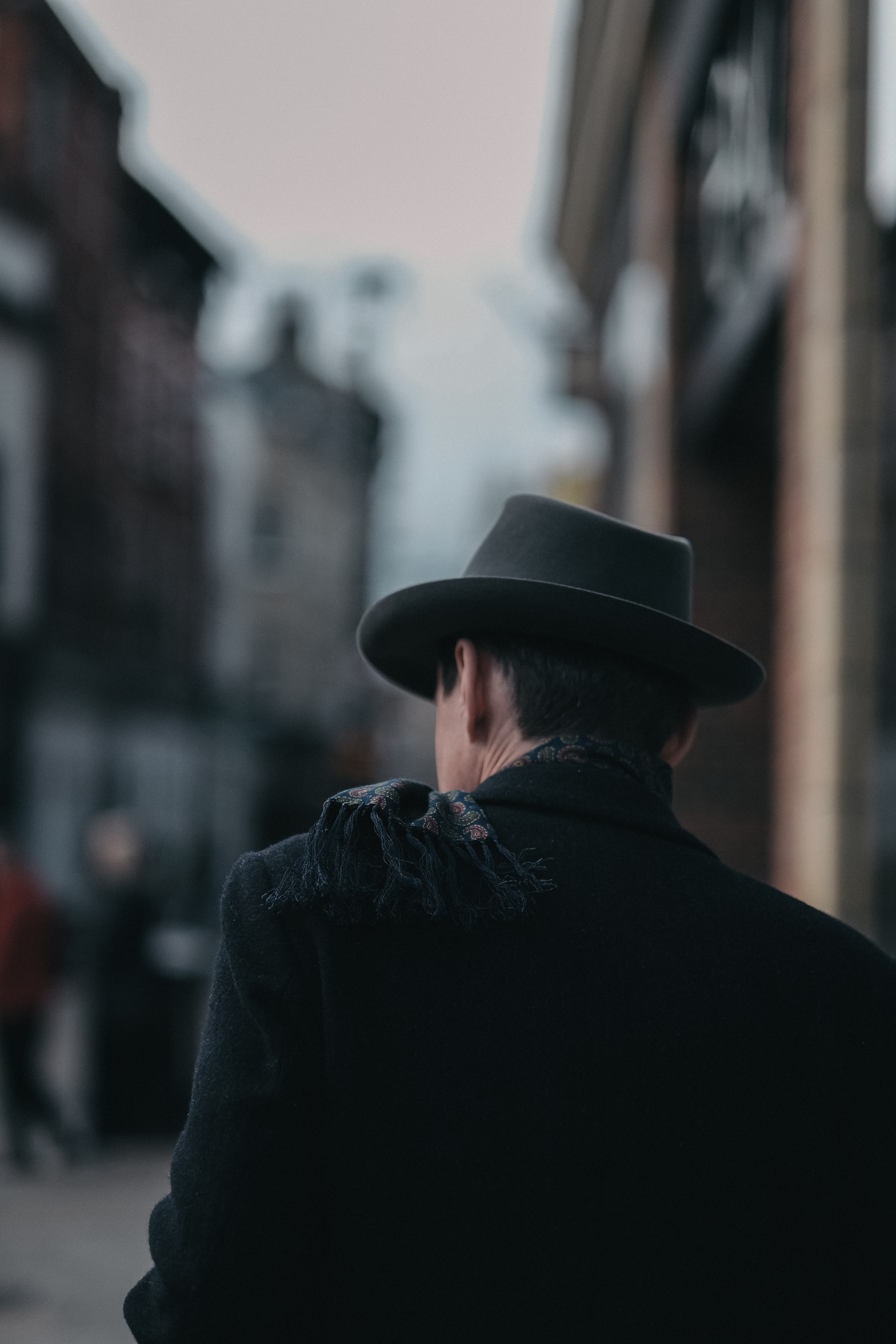 A shadowed man in a hat faces away on a blurred street in Cambridge