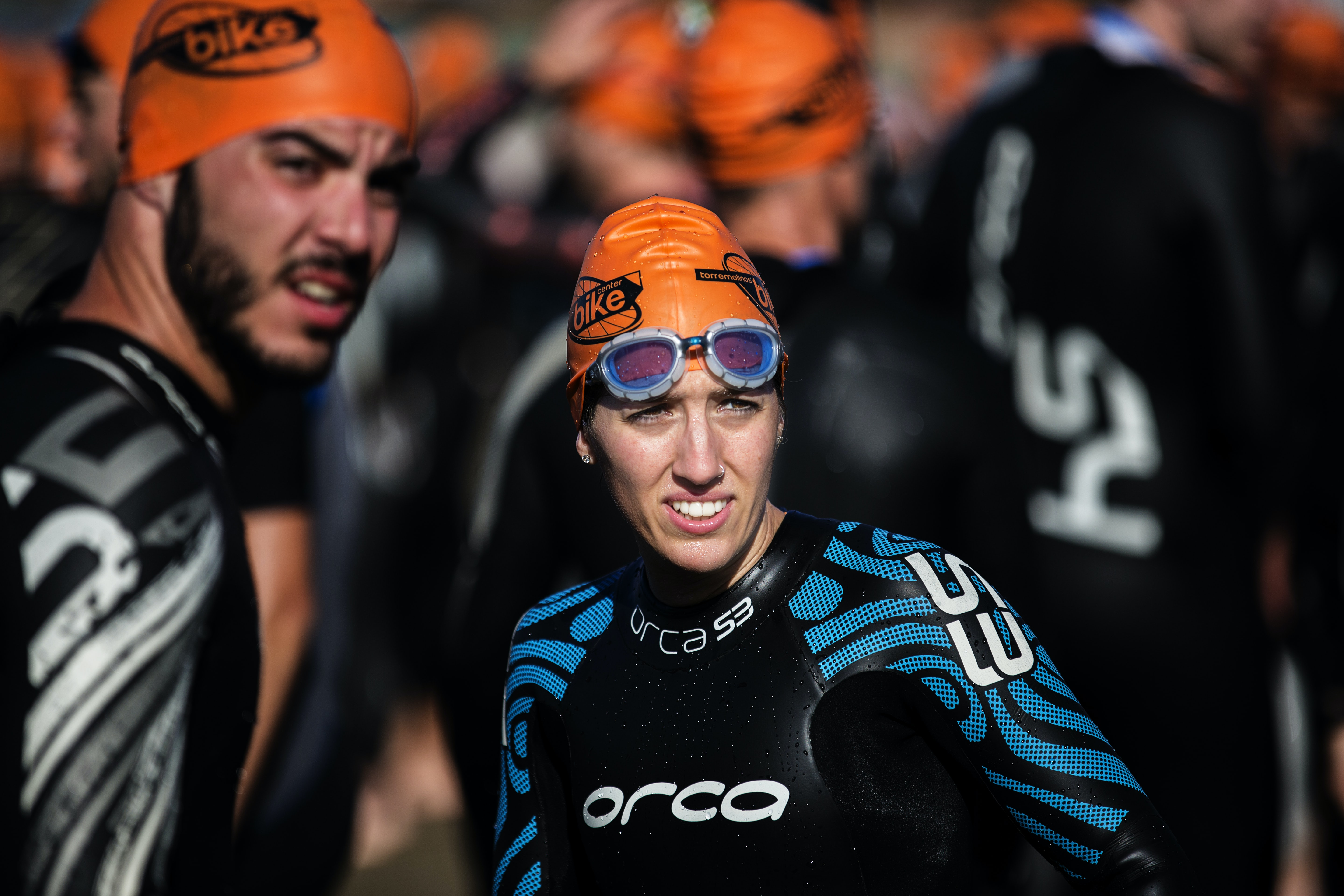 Triathletes wearing a wetsuit and goggles rest before a race