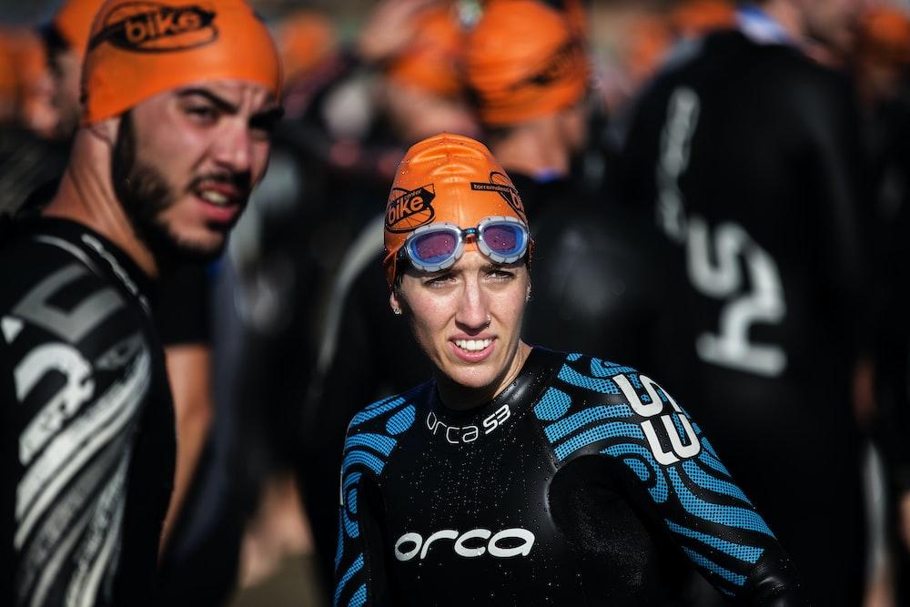 selective focus photography of woman wearing orange head cap and blue rashguard