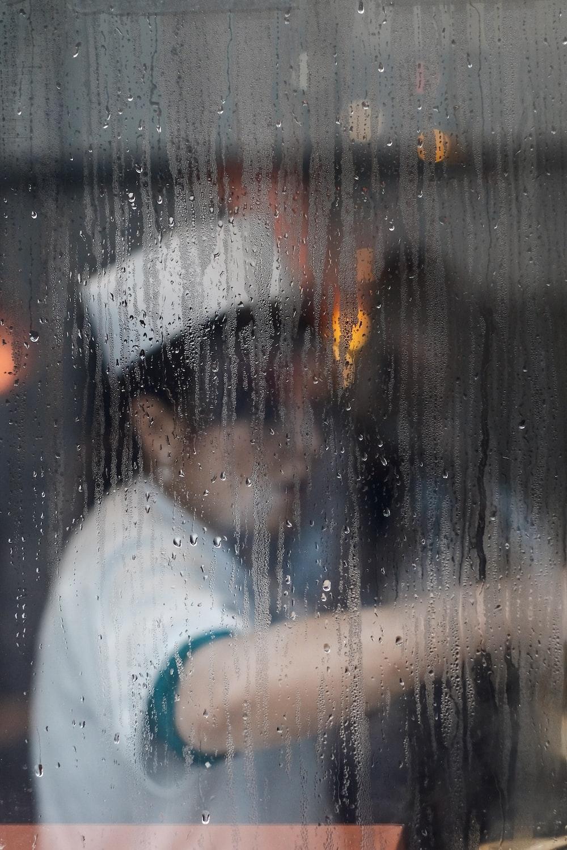 A cook at work seen through a rainy window